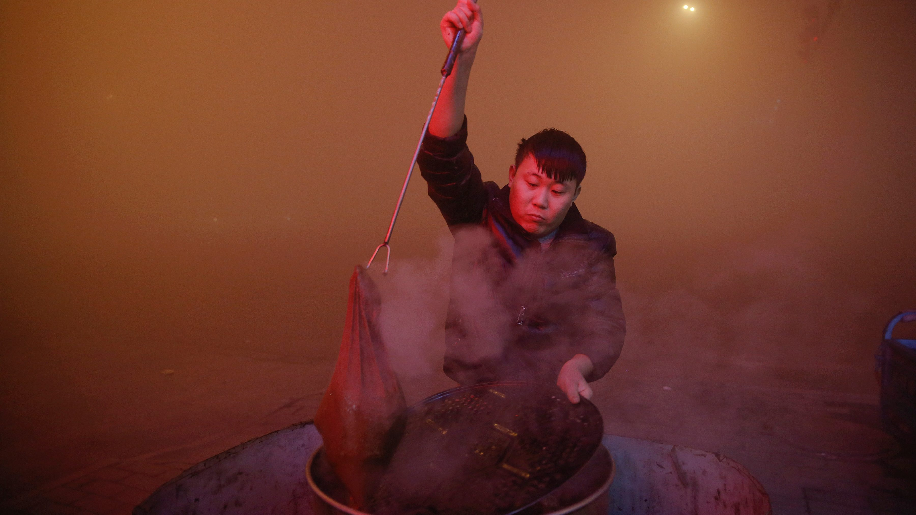 A man cooks in open air as heavy smog blankets Shengfang, in Hebei province, on an extremely polluted day with red alert issued, China December 19, 2016.