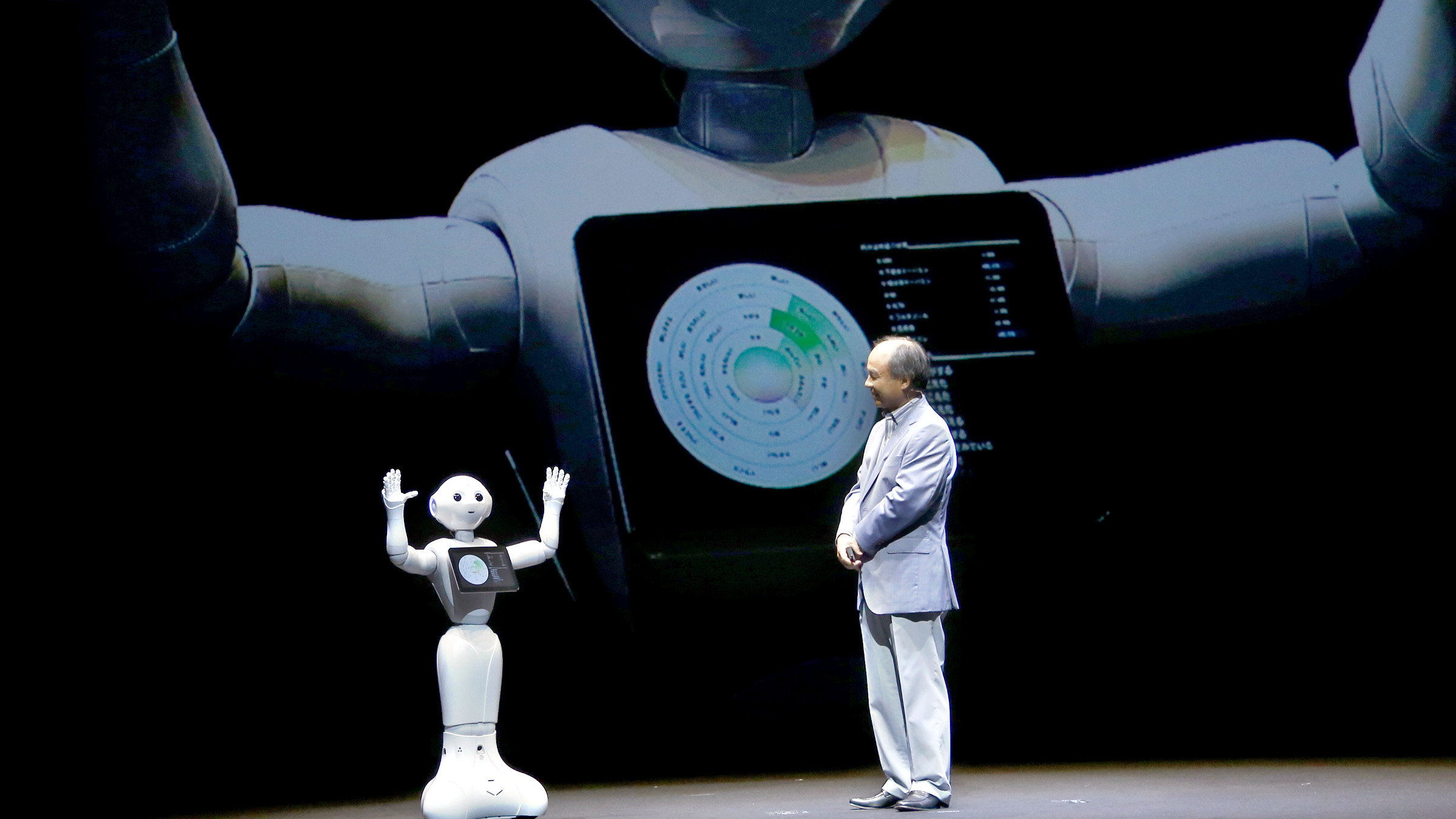 SoftBank Corp CEO Masayoshi Son speaks with the company's robot Pepper during a press conference in Maihama, near Tokyo, Thursday, June 18, 2015.