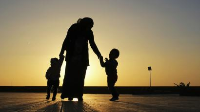 The silhouettes of a woman and her children against the sunset.