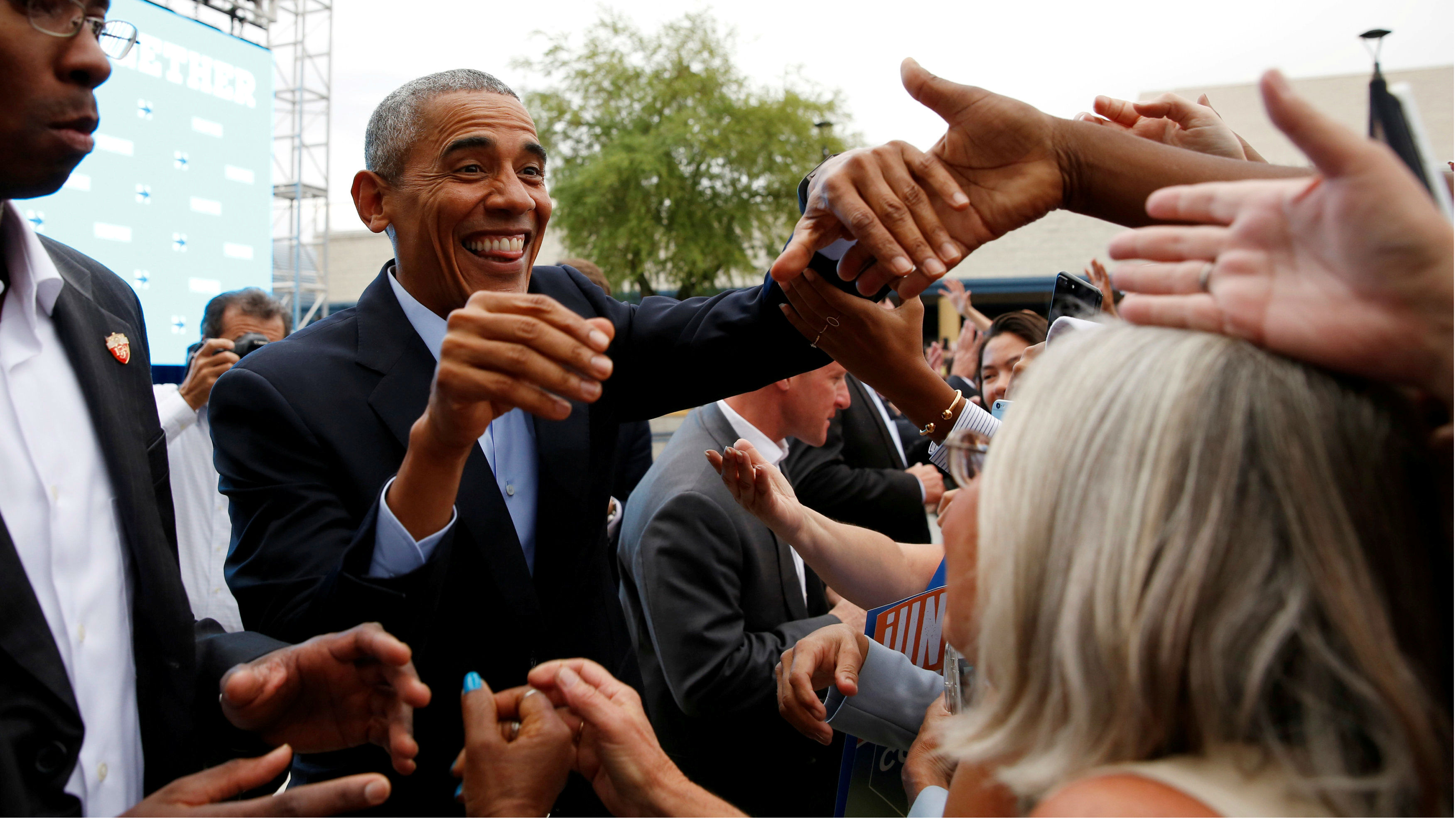 President Obama grins as he shakes the hands of supporters in a massive crowd.