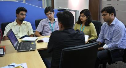 A woman employee attends a meeting with her male colleagues