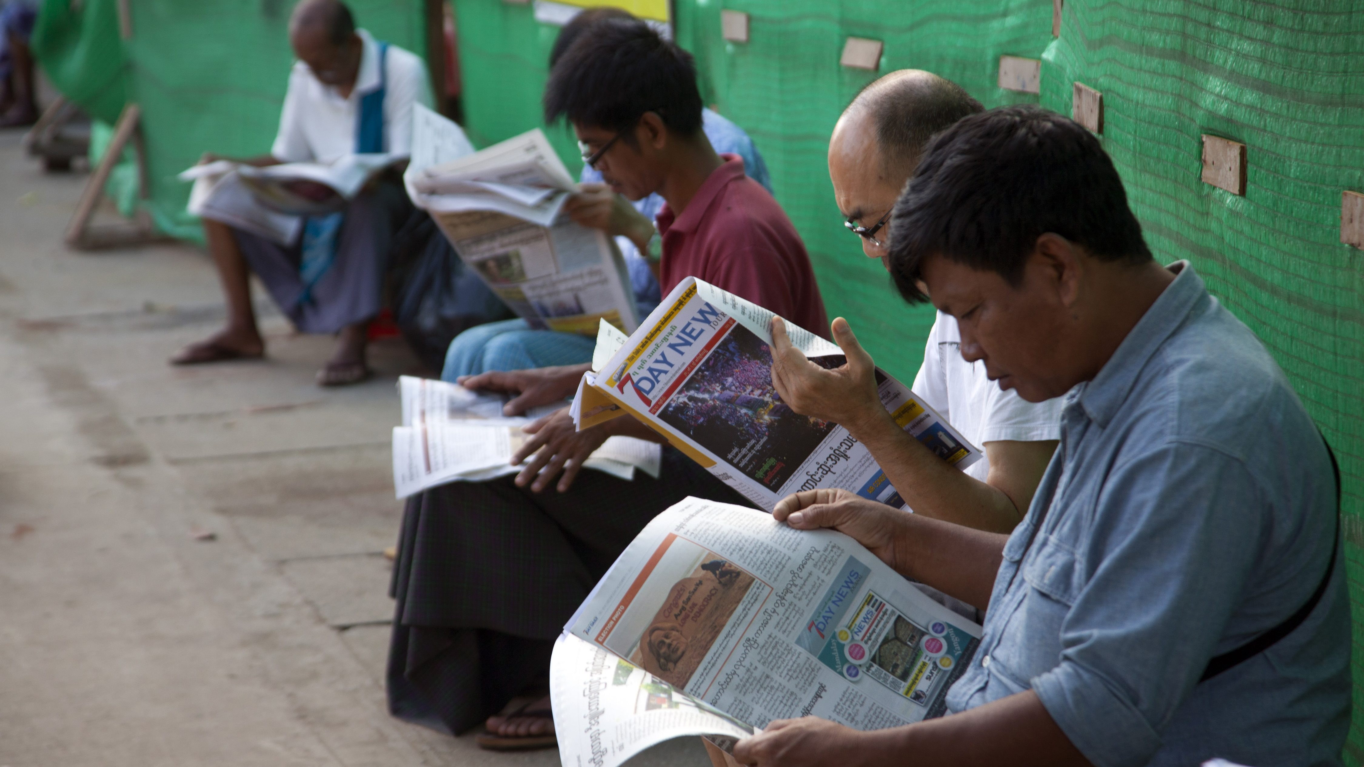 People read local newspapers at a roadside stand Wednesday, Nov. 11, 2015, in Yangon, Myanmar. Myanmar was trapped in a post-election limbo Tuesday with official results barely trickling in, although opposition leader Aung San Suu Kyi's party claimed a victory massive enough to give it the presidency and loosen the military's grip on the country. (AP Photo/Khin Maung Win)