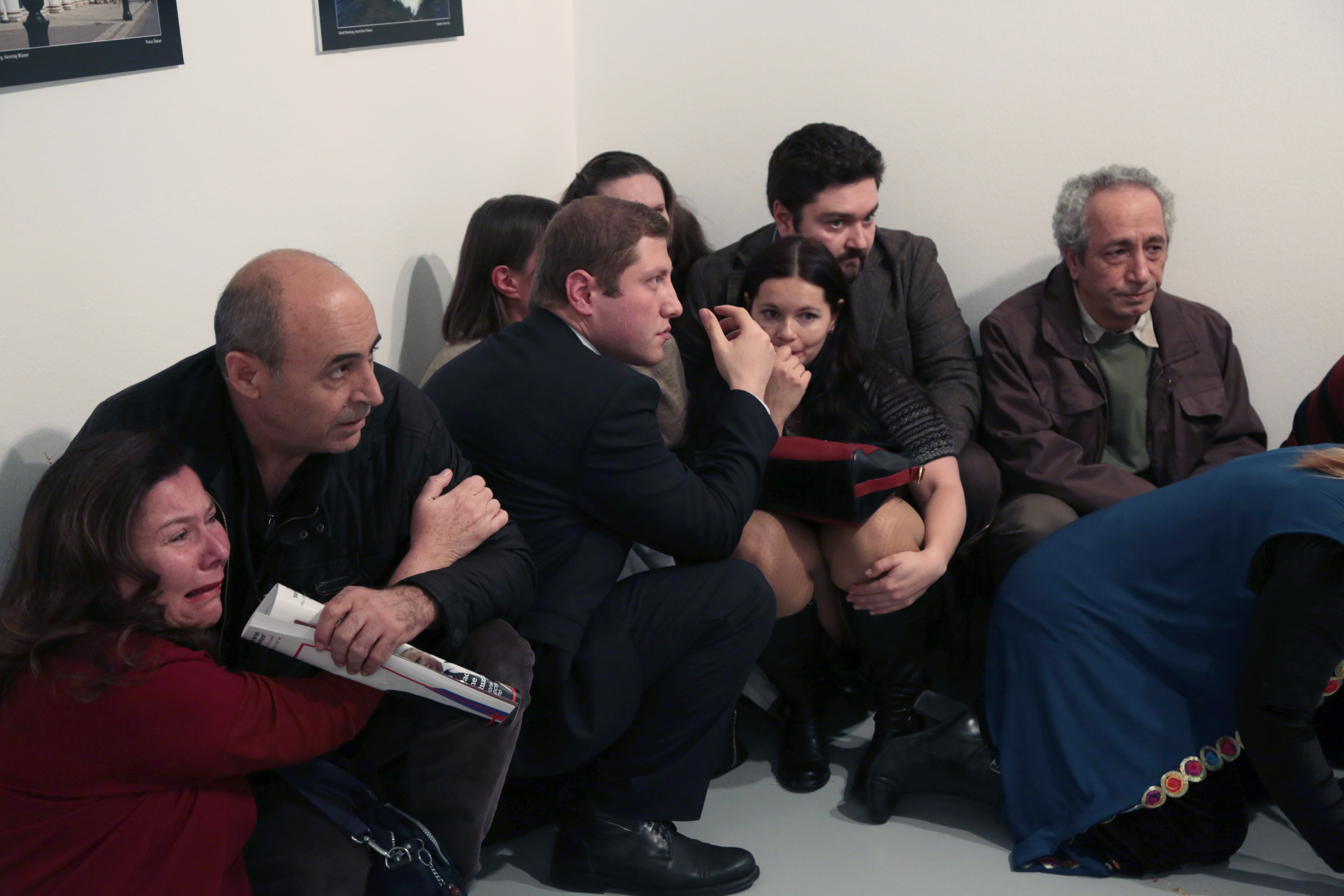 People crouch in a corner after Andrei Karlov, the Russian Ambassador to Turkey, was shot at a photo gallery in Ankara, Turkey on Dec.19,2016. Karlov, 62, was several minutes into a speech at an embassy-sponsored photo exhibition when a man fired a gun at him. Karlov was rushed to a hospital after the attack and later died from his gunshot wounds. (AP Photo/Burhan Ozbilici)