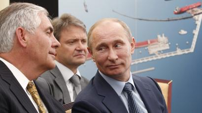 Russian President Vladimir Putin, right, and Exxon Mobil Corp. CEO Rex Tillerson, left, attend a signing ceremony of an agreement between state-controlled Russian oil company Rosneft and Exxon Mobil corporation at the Black Sea port of Tuapse, southern Russia, Friday, June 15, 2012. In the background is Krasnodar region governor Alexander Tkachev.