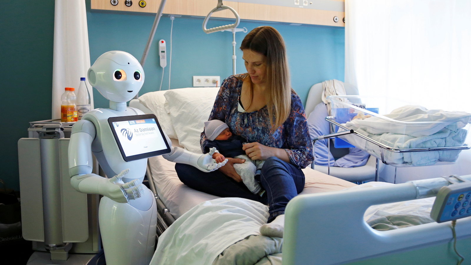 """New recruit """"Pepper"""" the robot, a humanoid robot designed to welcome and take care of visitors and patients, holds the hand of a new born baby next to his mother at AZ Damiaan hospital in Ostend, Belgium June 16, 2016. REUTERS/Francois Lenoir     TPX IMAGES OF THE DAY      - RTX2GKIO"""
