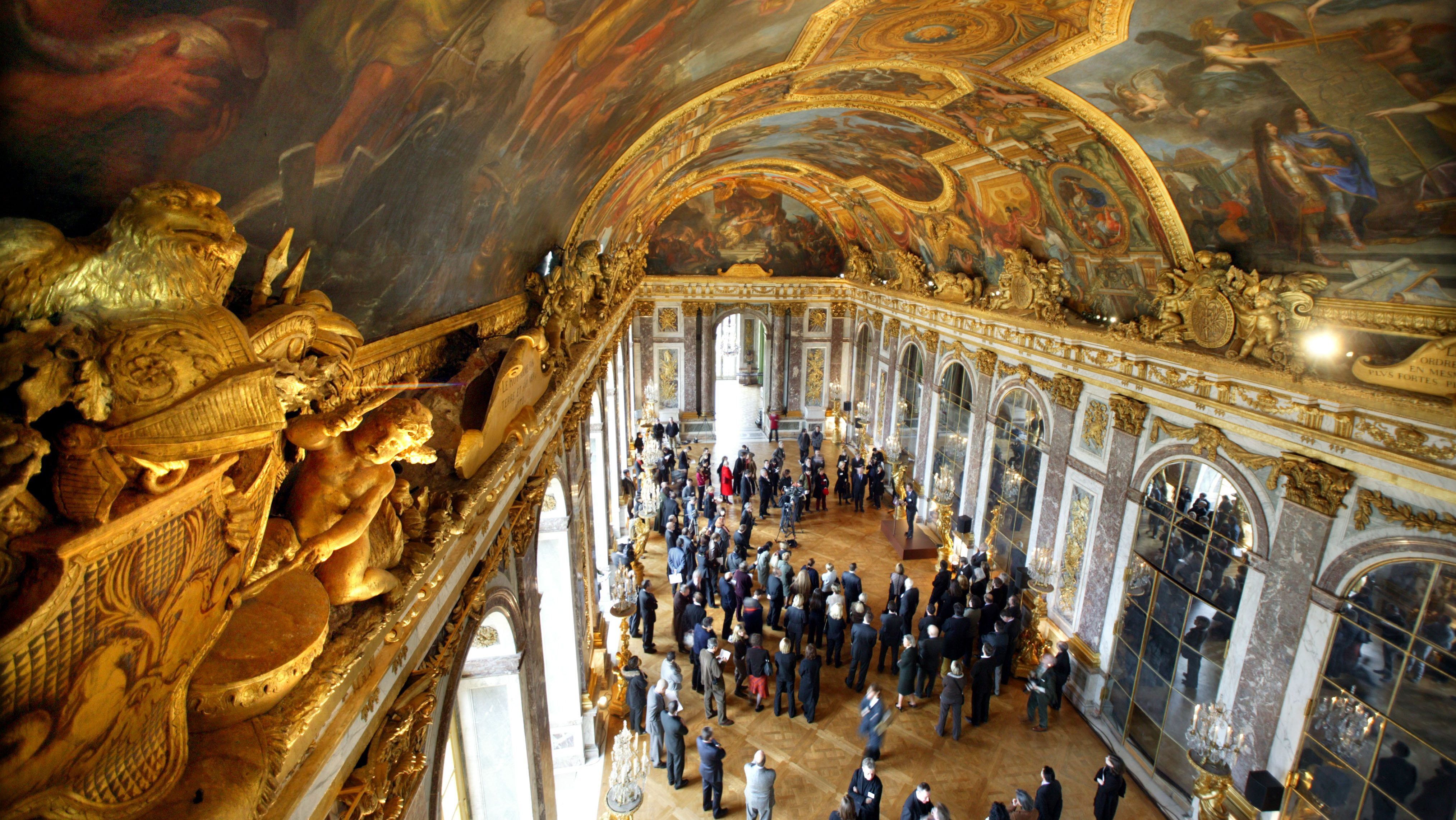 Guests visit the newly restored part of the Hall of Mirrors on its opening day at the Versailles Palace near Paris December 19, 2005. The first part of the Hall of Mirrors restoration was completed after 20 months of works, the restoration of the second part will start in February 2006. REUTERS/Charles Platiau - RTR1BAHH