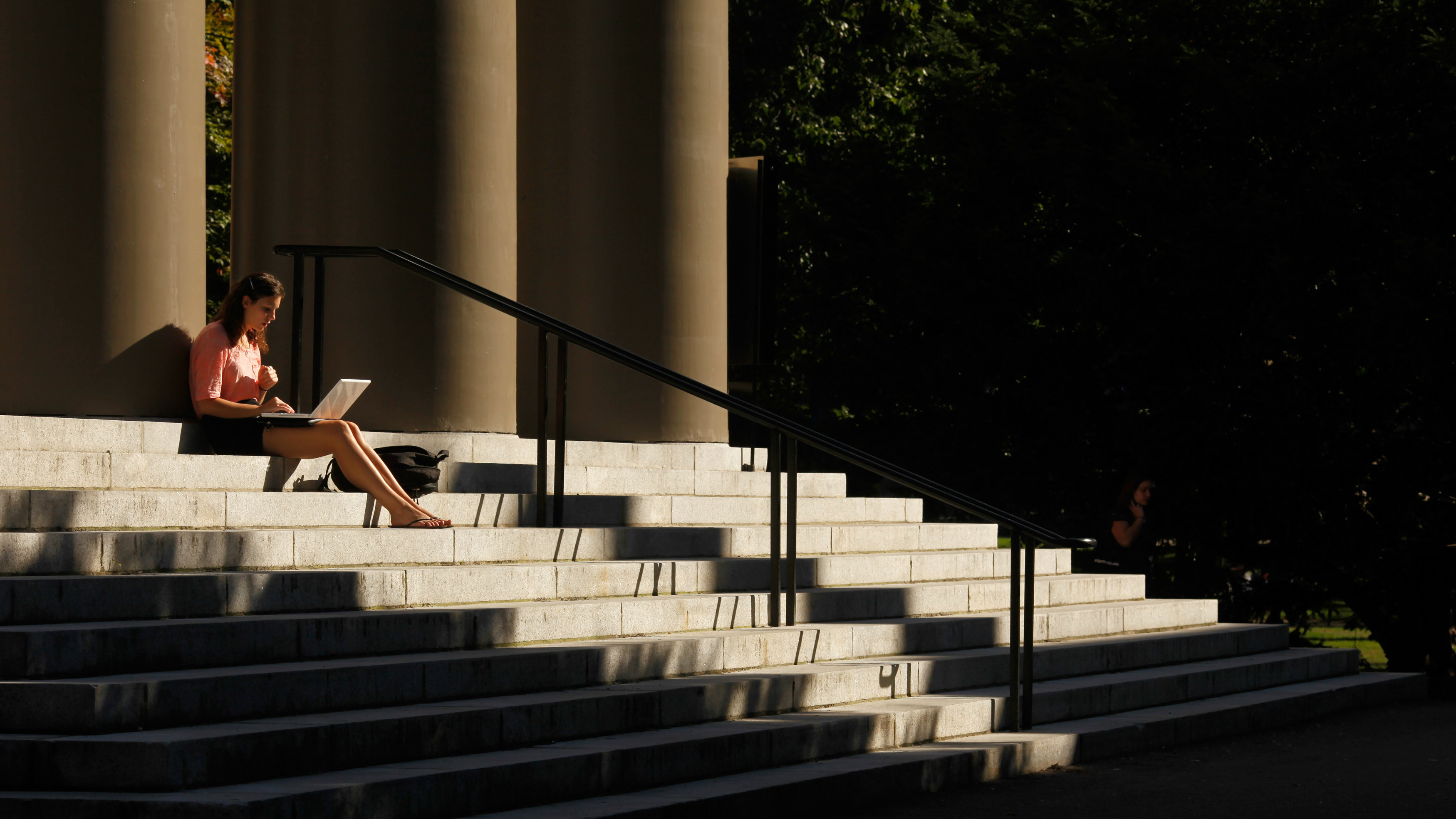 A student uses her laptop computer on the steps to Memorial Church at Harvard University in Cambridge...
