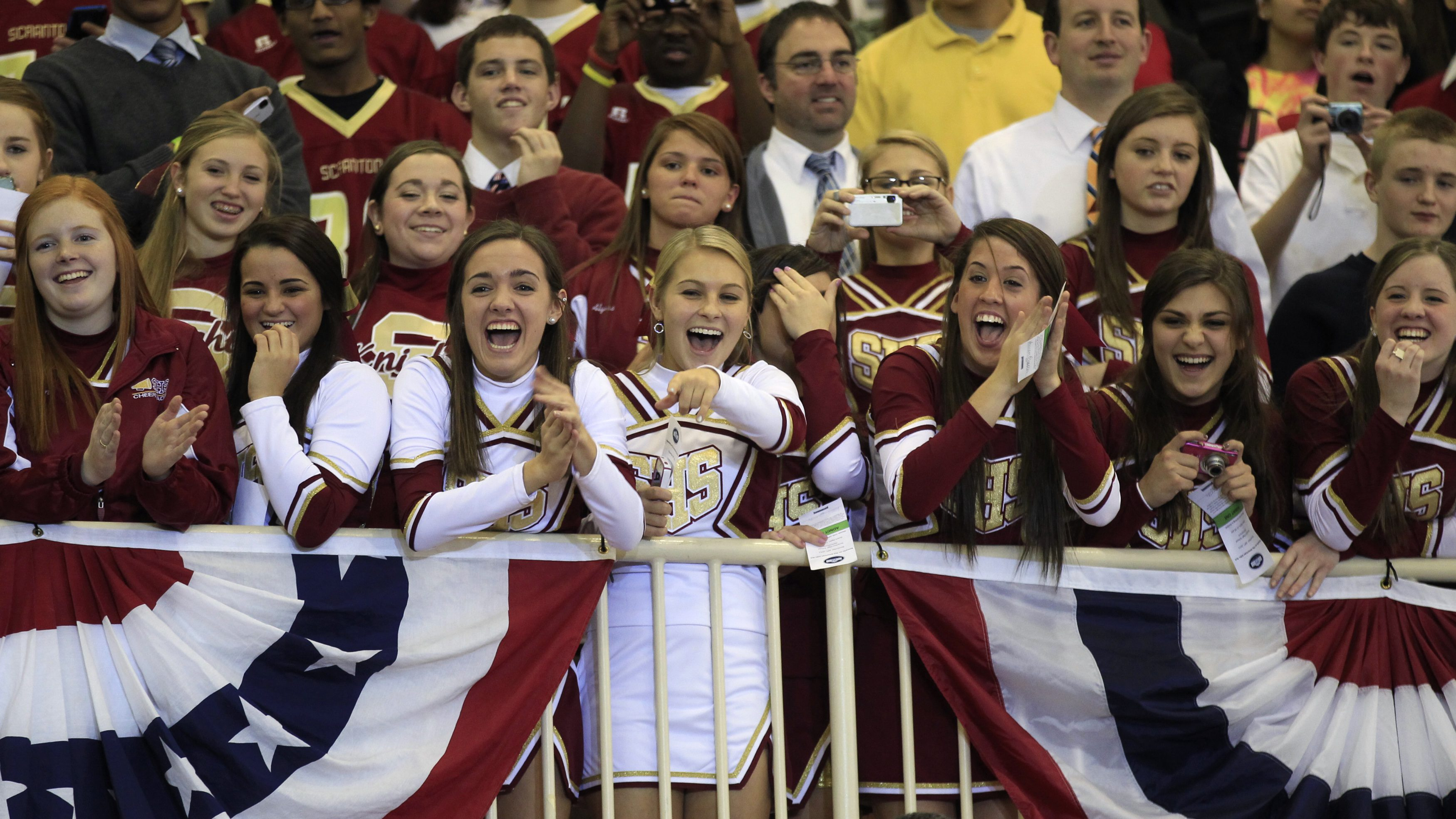 Cheerleaders at Scranton High School react as U.S. President Barack Obama shakes hands with people after talking about extending and expanding the payroll tax cut during his visit to Scranton, Pennsylvania November 30, 2011.