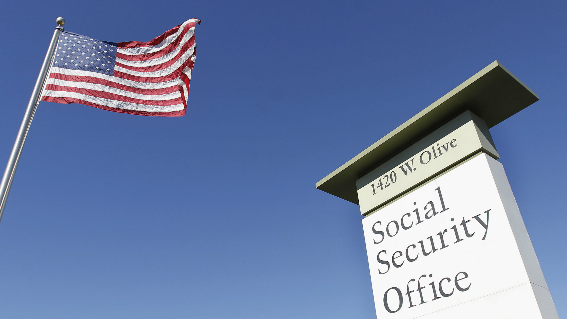 An American flag flutters in the wind next to signage for a United States Social Security Administration in California