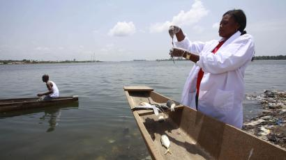 An African researcher in a canoe collecting water samples.