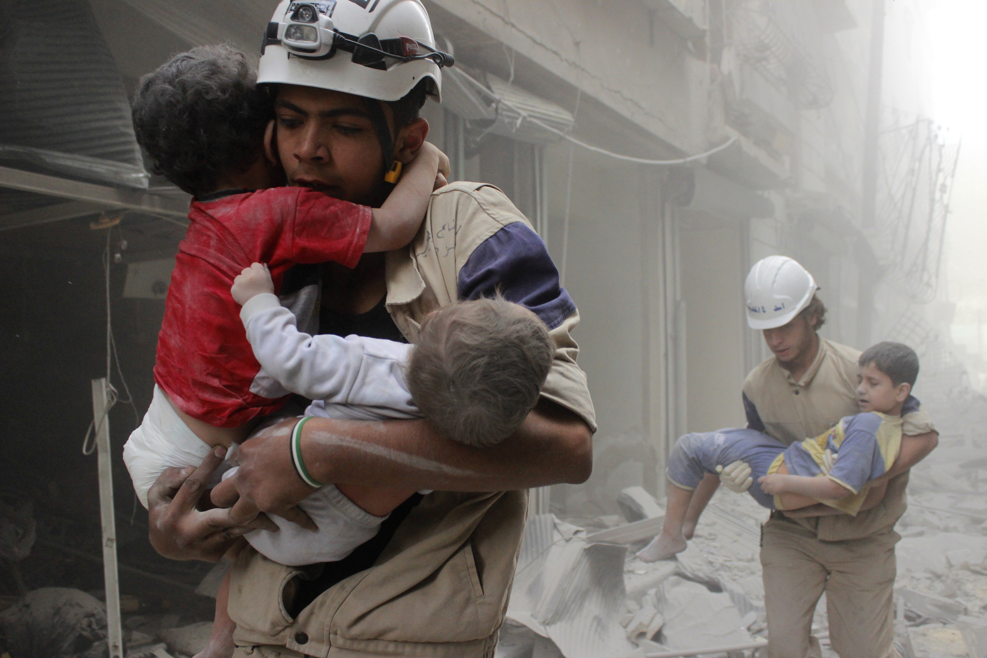 Members of the Civil Defence rescue children after what activists said was an air strike by forces loyal to Syria's President Bashar al-Assad in al-Shaar neighbourhood of Aleppo June 2, 2014.