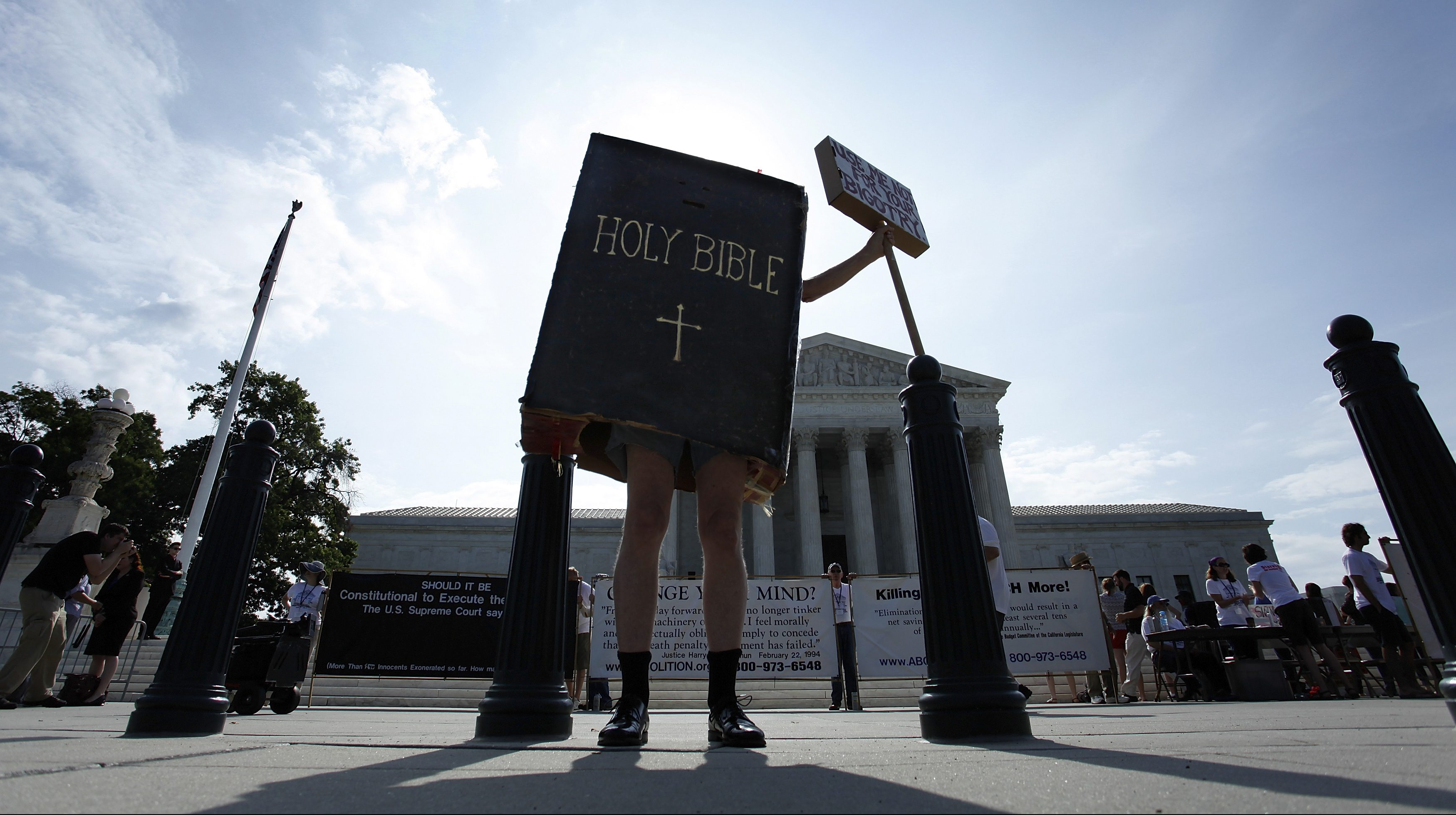 A protester dressed as a copy of the Bible joins groups demonstrating outside the U.S. Supreme Court in Washington June 30, 2014. The U.S. Supreme Court on Monday ruled that business owners can object on religious grounds to a provision of U.S. President Barack Obama's healthcare law that requires closely held companies to provide health insurance that covers birth control. REUTERS/Jonathan Ernst (UNITED STATES - Tags: RELIGION HEALTH CIVIL UNREST POLITICS TPX IMAGES OF THE DAY) - RTR3WG97