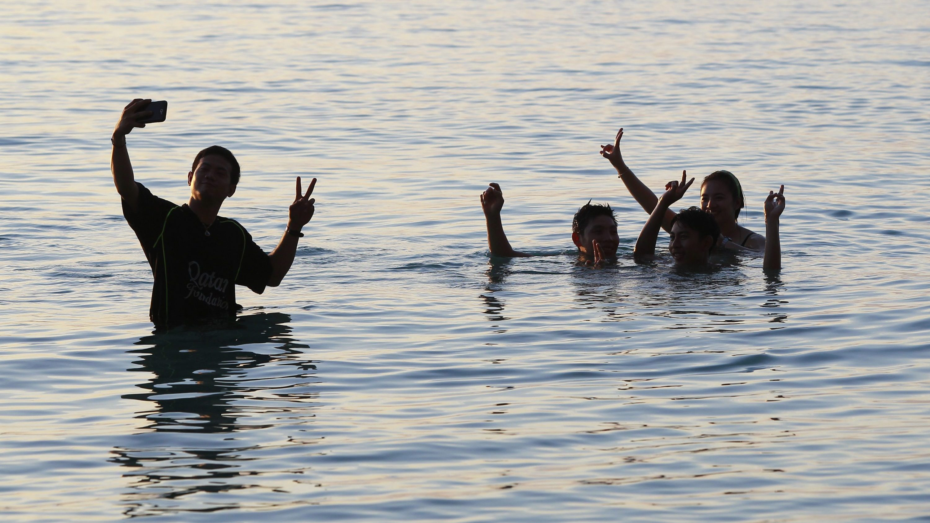 """Tourists pose for a """"selfie"""" during sunset by the island of Koh Tao September 20, 2014."""