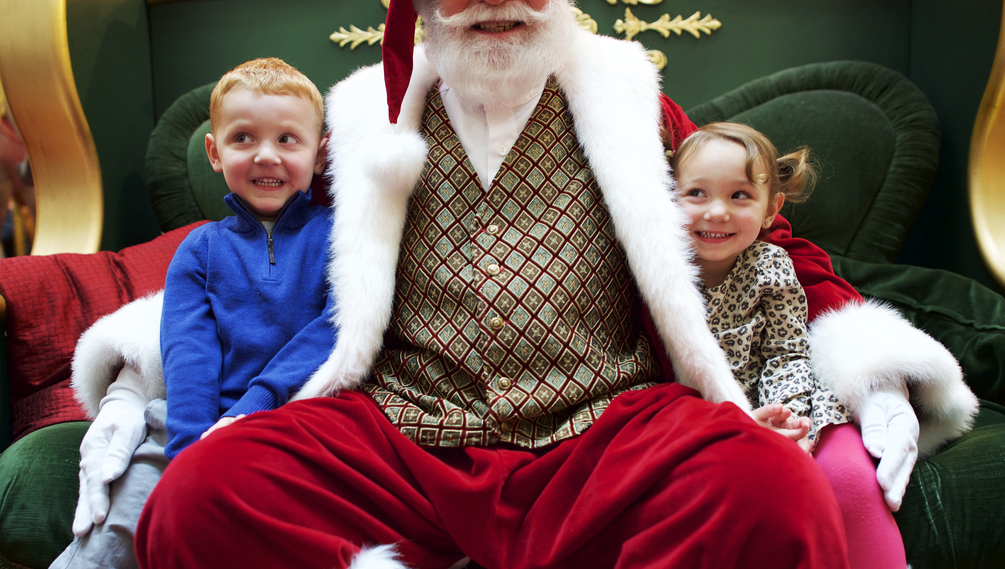 Brother and sister, Brynlie, 4, and Brayden, 2, Knowles (L-R) sit on Santa Claus's lap for a portrait at The Plaza, King of Prussia Mall, United State's largest retail shopping space, in King of Prussia, Pennsylvania on December 6, 2014.  The 2.7 million square feet shopping destination is owned by Simon Property Group. Picture taken December 6, 2014.  REUTERS/Mark Makela (UNITED STATES - Tags: BUSINESS) - RTR4H1BV