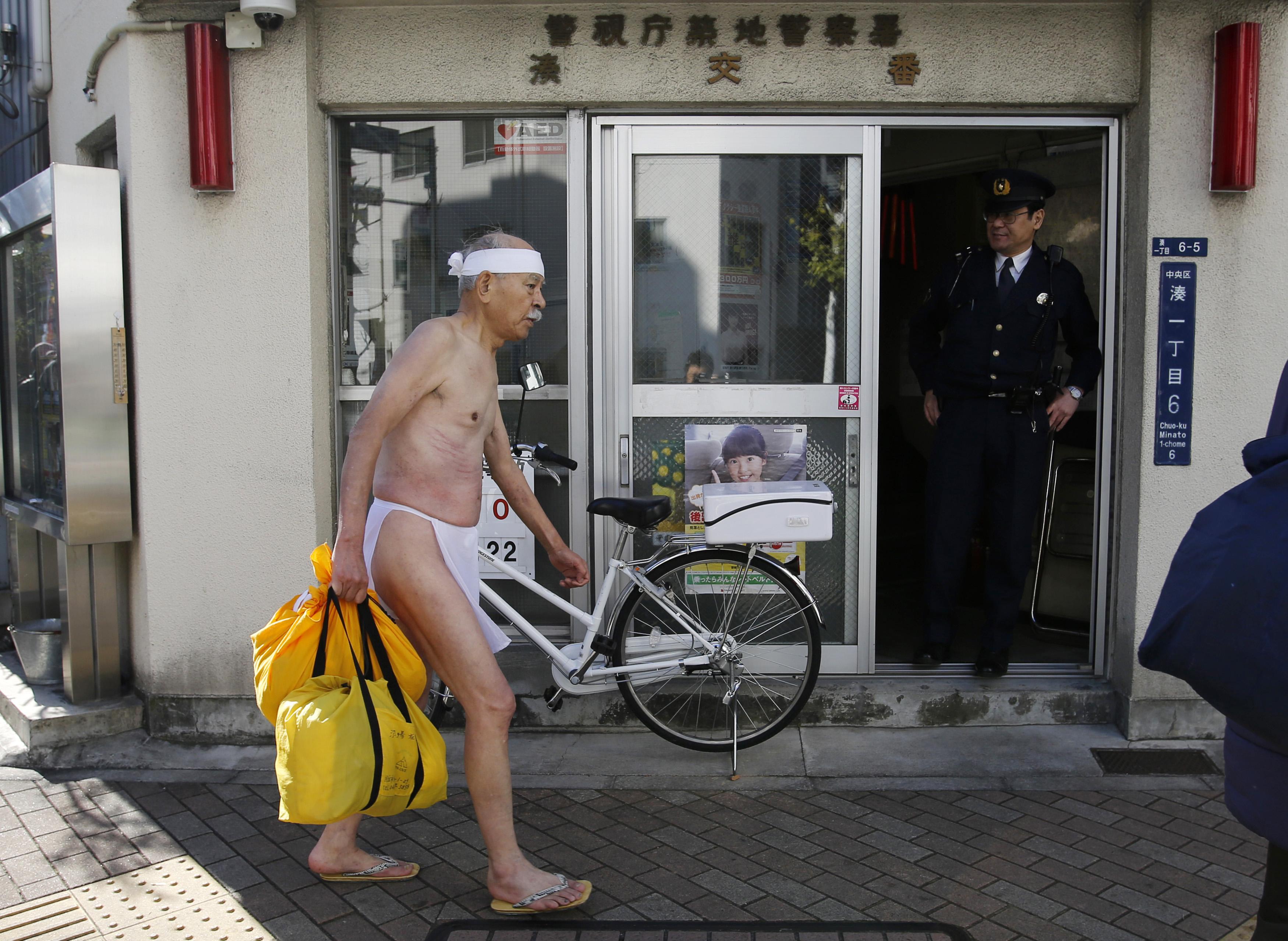A Japanese man on his way to take a (Shinto ritual) bath in a loin cloth.