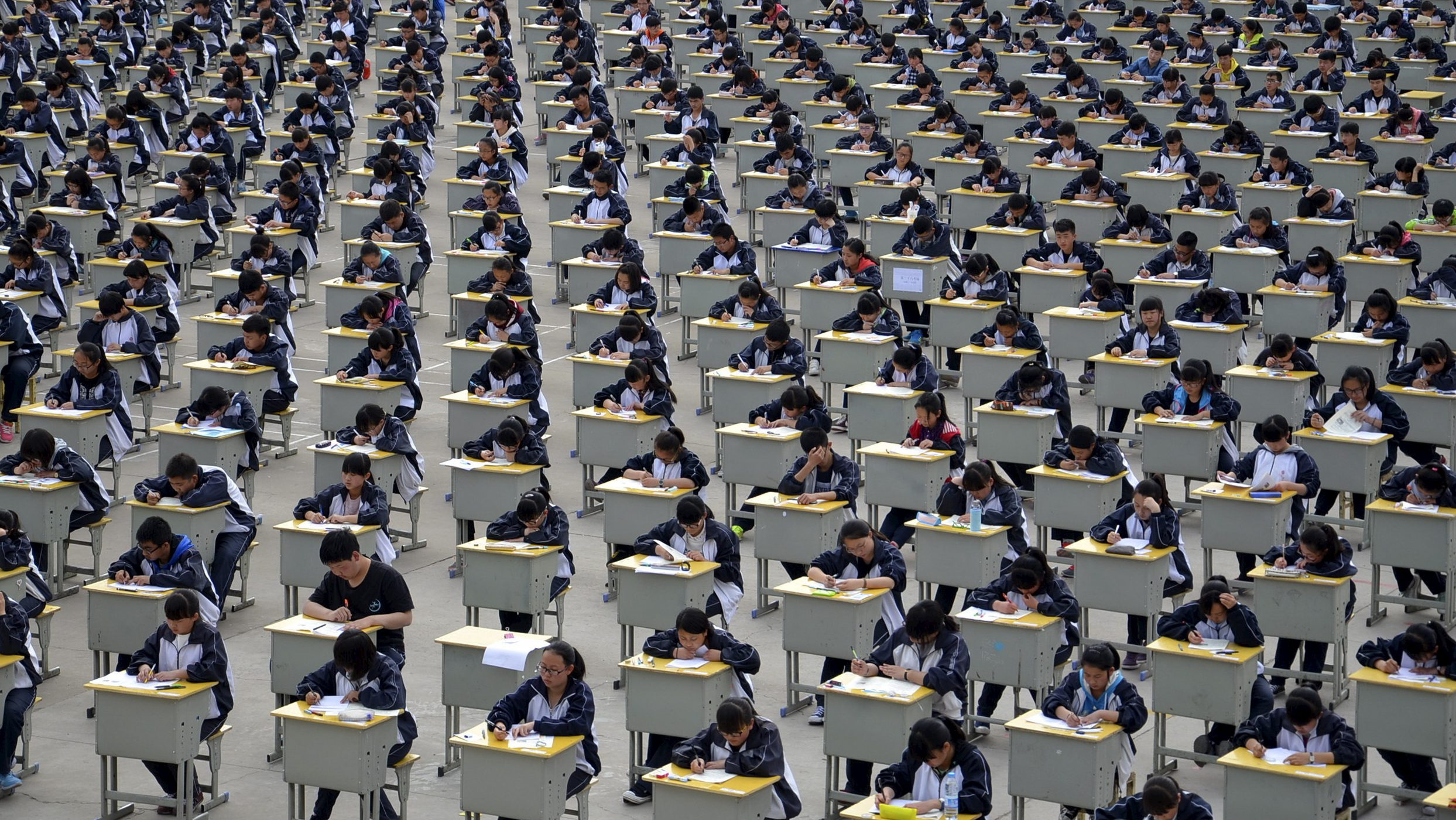 Students take an examination on an open-air playground at a high school in Yichuan, Shaanxi province April 11, 2015. More than 1,700 freshmen students took part in the exam on Saturday, which was the first attempt by the school to take it in open-air. The school said the reasons was due to the insufficient indoor space and also that it could be a test of the students' organizing capacity, local media reported. Picture taken April 11, 2015. REUTERS/Stringer      TPX IMAGES OF THE DAY      - RTR4WYSJ