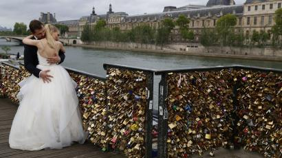 """A recently-married couple embrace near grills covered with """"love locks"""""""