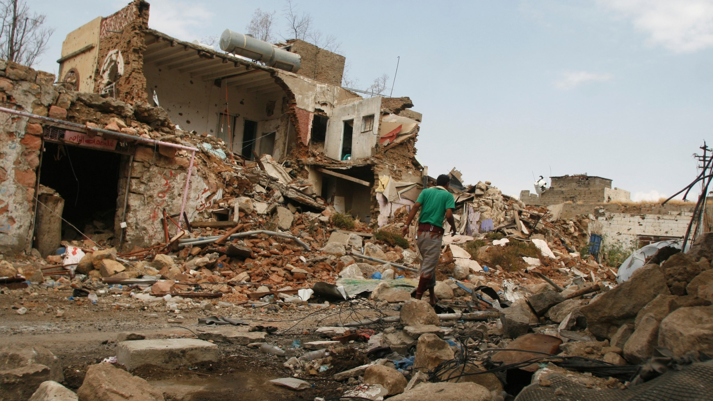 A man walks by a destroyed house