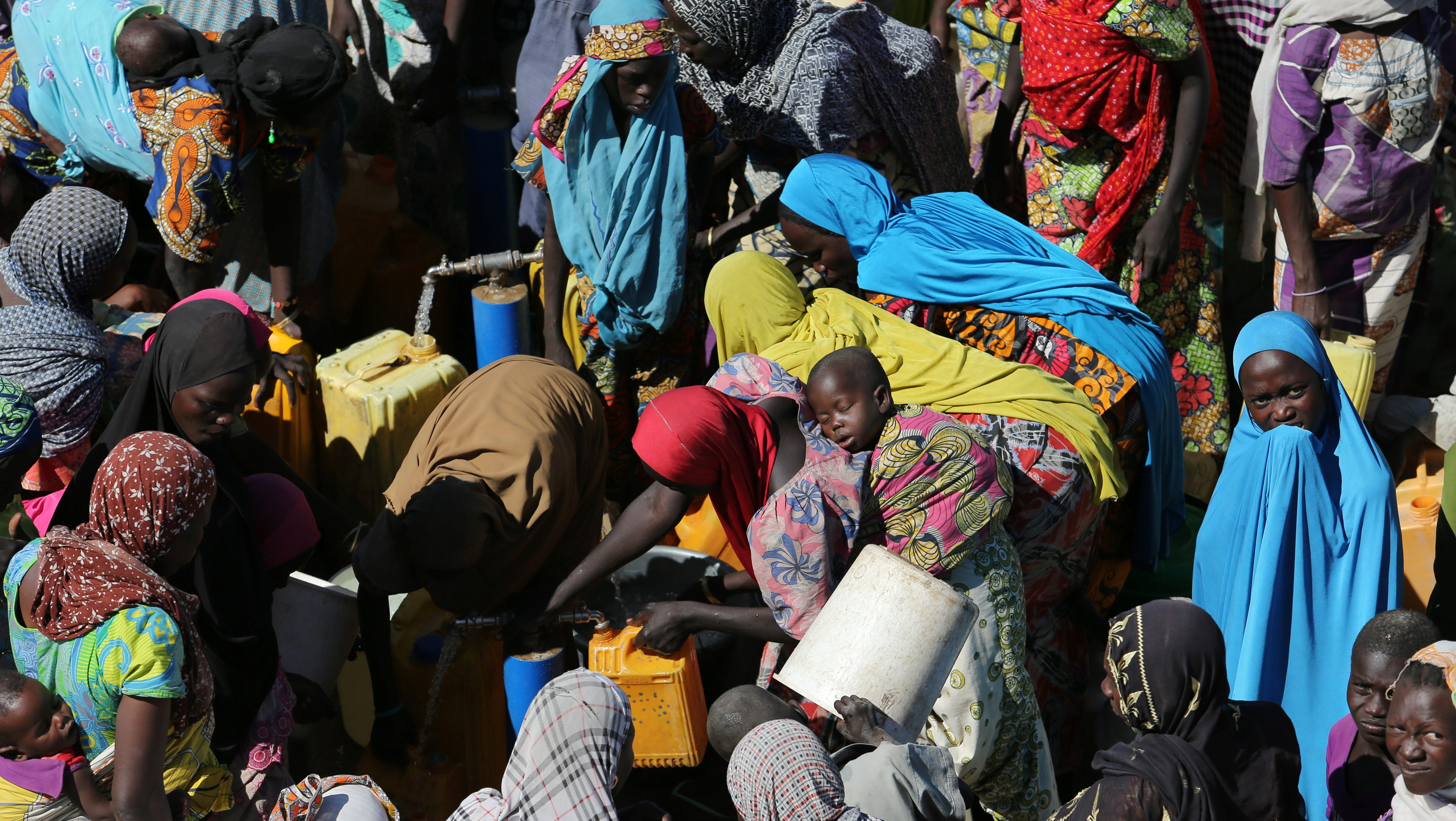 Women gather to collect water at a motorised borehole at the Muna Internally displace people camp in Maiduguri, Nigeria