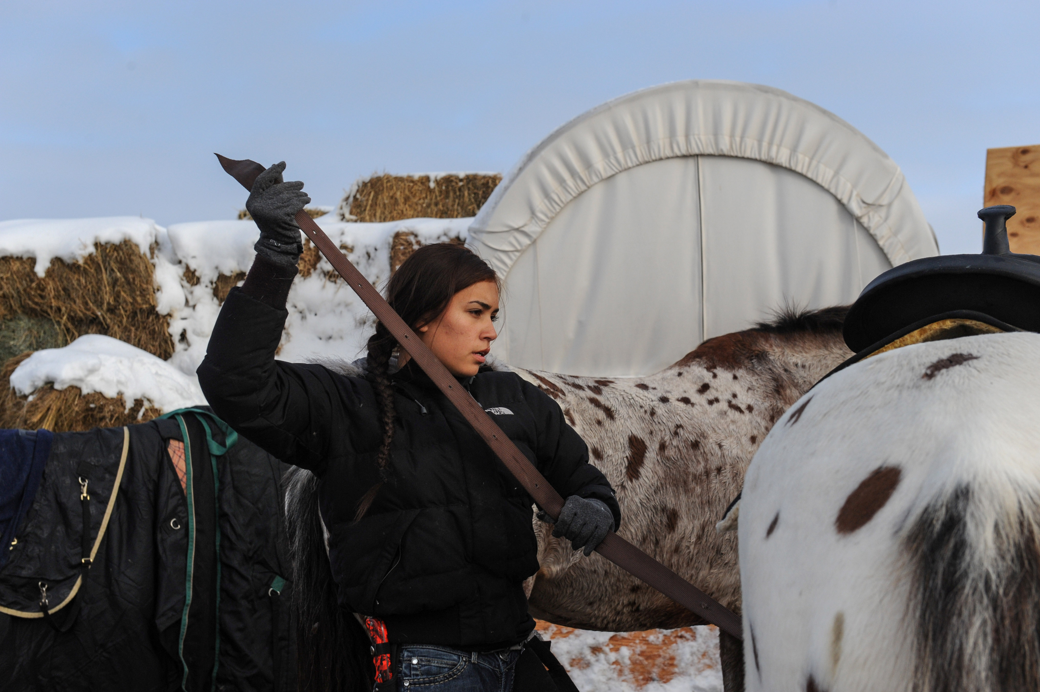 Waskoness Pitswanakwat, 16, puts a saddle on her horse in Oceti Sakowin camp during a protest against plans to pass the Dakota Access pipeline near the Standing Rock Indian Reservation, near Cannon Ball, North Dakota, U.S. December 2, 2016. REUTERS/Stephanie Keith - RTSUF9W