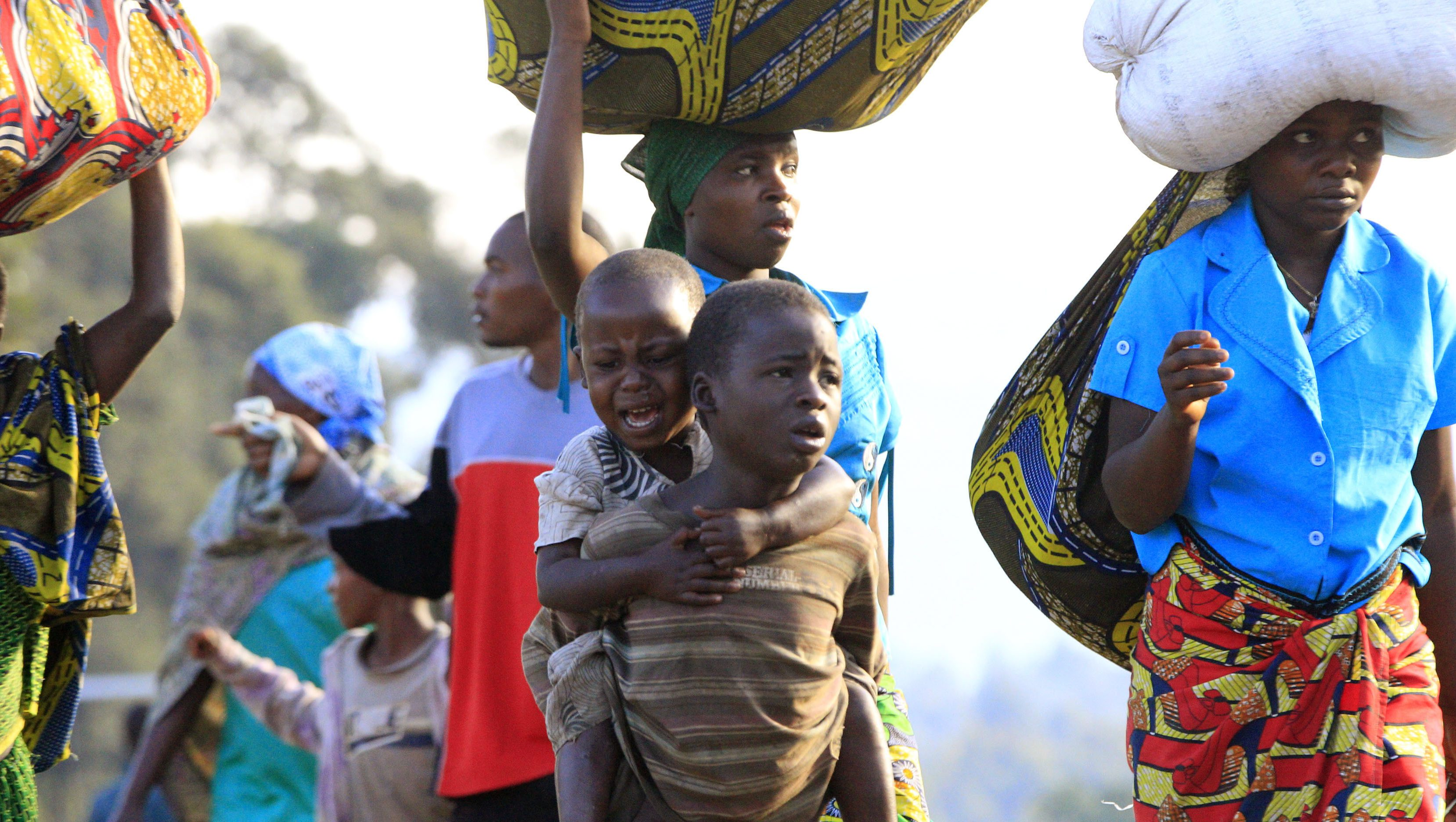A boy, displaced by fighting between the Congolese army and M23 rebels in Bunagana in the eastern Democratic Republic of Congo, carries a crying child on his back as they make their way home after spending a night in the Ugandan town of Bunagana, 491 km (305 miles) west of capital Kampala October 31, 2013. Civilians celebrated in the streets on Wednesday as Congolese troops entered the eastern border town of Bunagana after a major new success in their offensive to crush a 20-month rebellion. The town was the first seized last year by M23 rebels in the Democratic Republic of Congo and the last they held after being forced back recently by Congo's U.N.-backed army. Bunagana was strategic during the rebellion, allowing the M23 to control lucrative cross-border taxation and giving them access to Uganda and Rwanda, which are accused by U.N. experts of backing the rebels, something both nations deny.