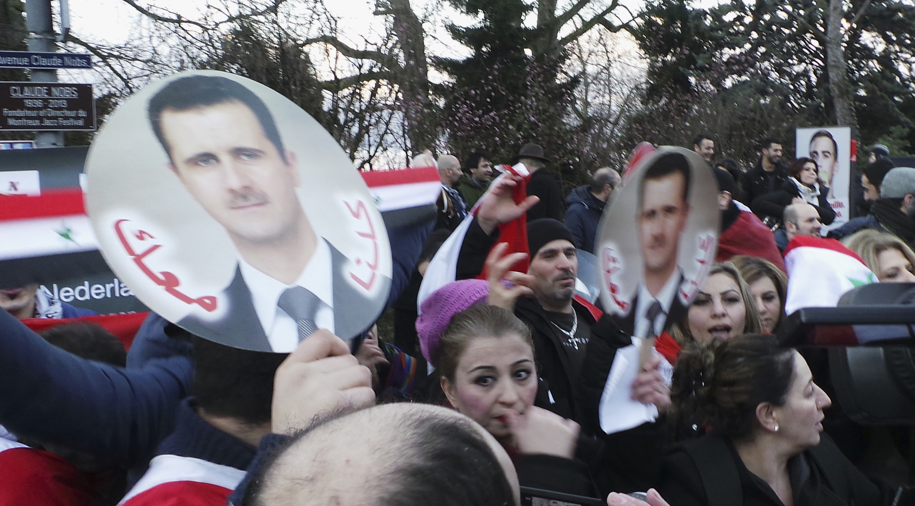 """A pro-Assad demonstrator carråy portraits of Syrian President Bashar al-Assad in front of the venue where the Syria peace conference is held, in Montreux January 22, 2014. Syria's government and opposition, meeting face to face for the first time at a U.N. peace conference, angrily spelled out their hostility on Wednesday as world powers also restated contrasting views on the future of President Bashar al-Assad. Signs read, """"We are all with you""""."""