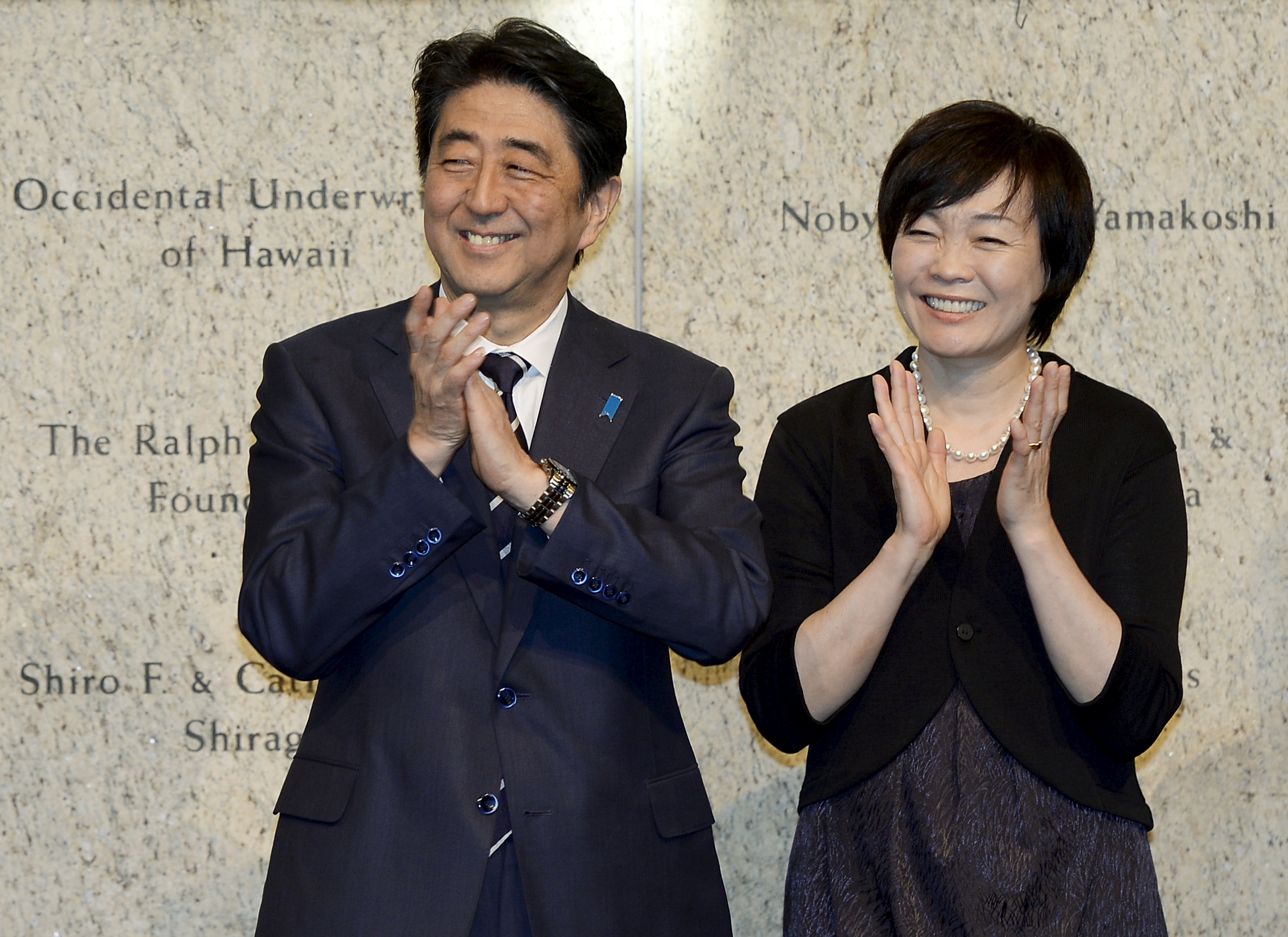 Japan's Prime Minister Shinzo Abe (L) and his wife Akie Abe applaud during a reception at the Japanese American National Museum in Los Angeles