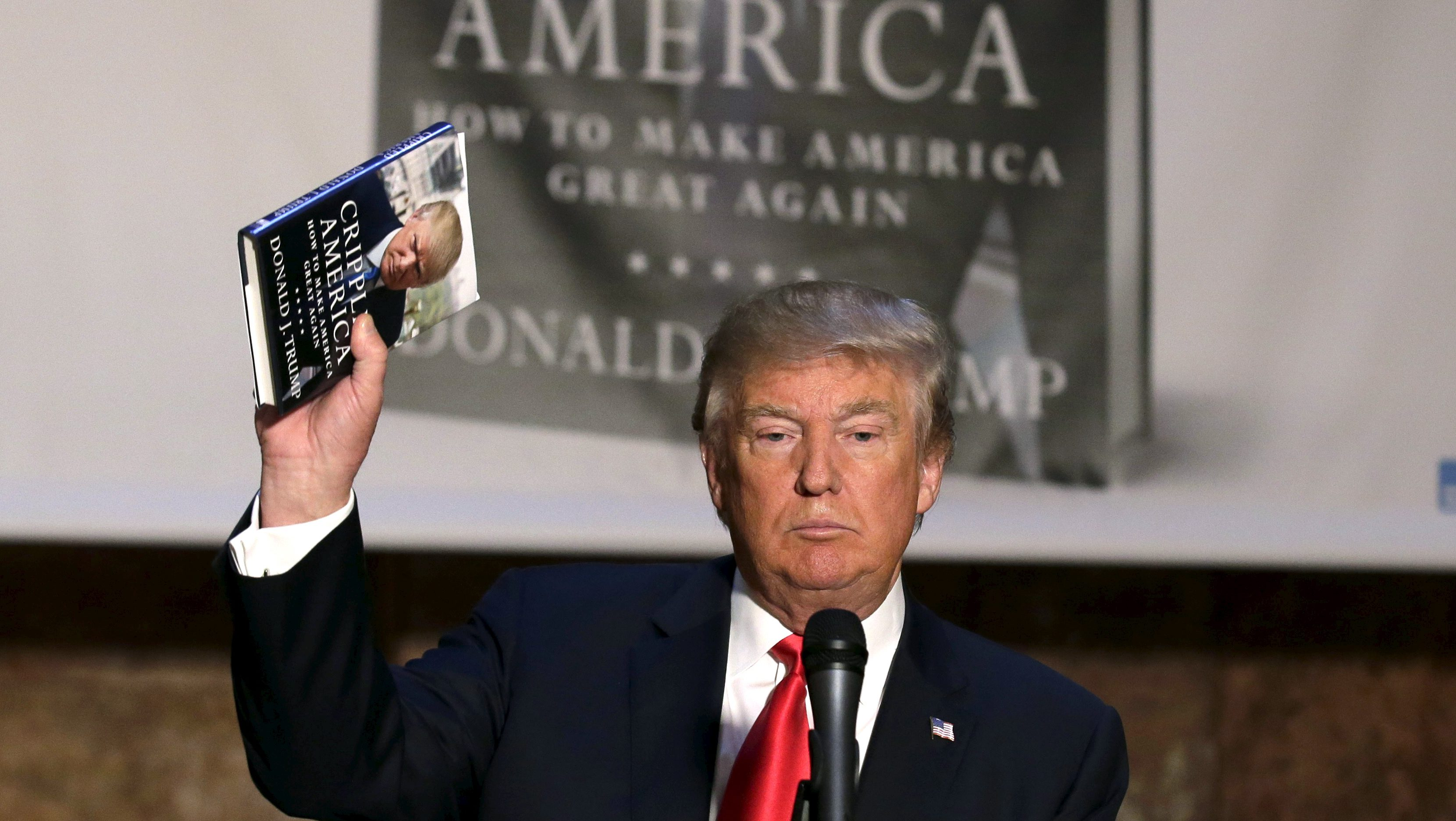 "Republican presidential candidate Donald Trump holds up a copy of his new book ""Crippled America"" at news conference to promote the book in the Manhattan borough of New York City, November 3, 2015.  REUTERS/Brendan Mcdermid      TPX IMAGES OF THE DAY           TPX IMAGES OF THE DAY      - RTX1UL4V"