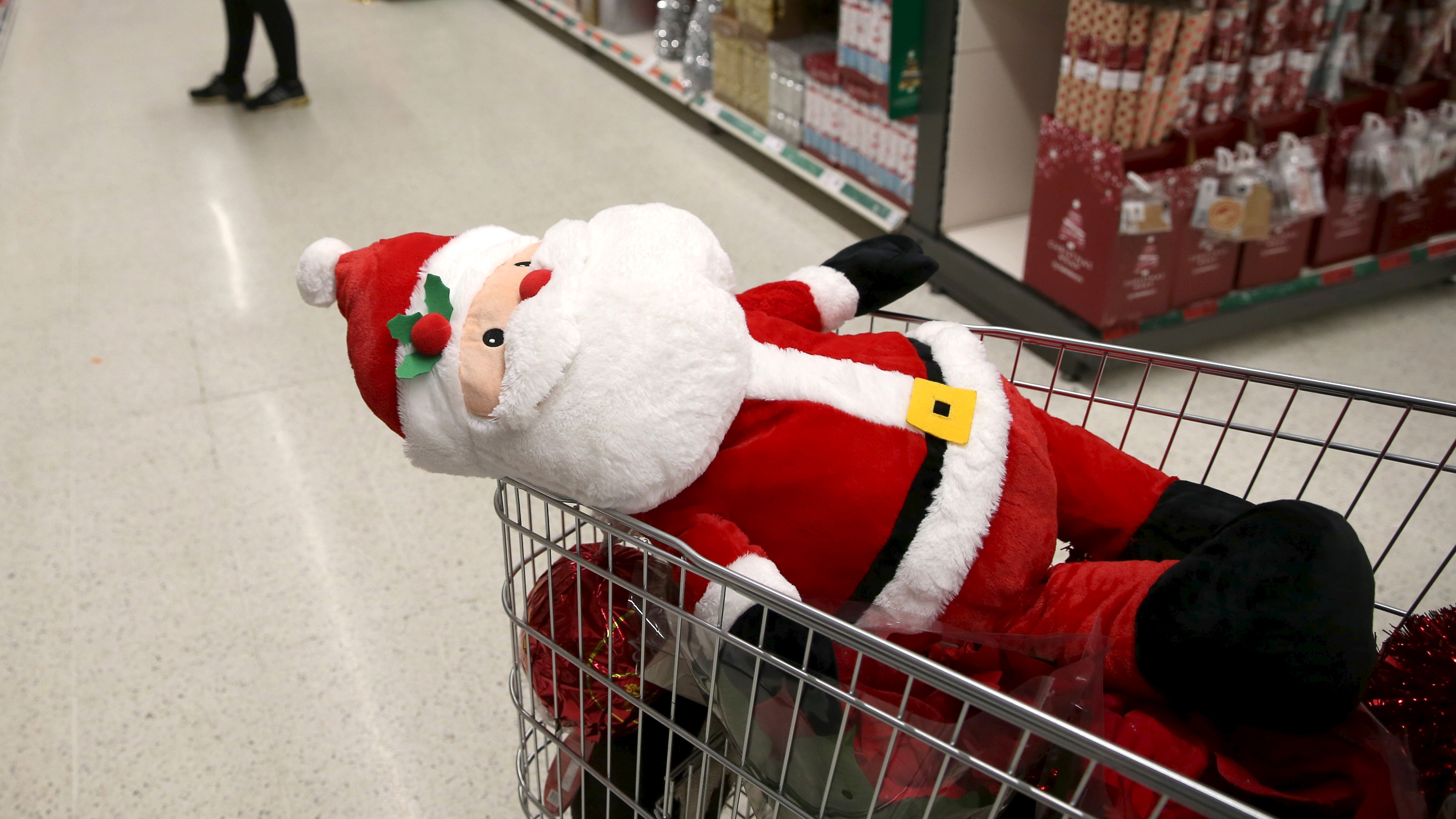 A stuffed santa toy is seen in a shopping trolley at a Sainsbury's store in London December 3, 2015. Britons will spend 20.3 billion pounds ($31 billion) on groceries over the festive period, a 1.4 percent increase on last year, industry research group IGD forecast on Wednesday. The group said its research found 19 percent of shoppers plan to spend more on food and drink over the Christmas period, defined as Nov. 20 to Dec. 26, than the previous Christmas, a trend which could be positive for the likes of market leaders Tesco and Sainsbury. REUTERS/Neil Hall