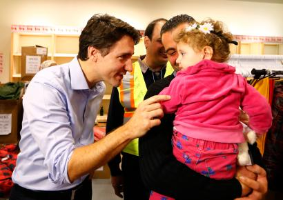 Syrian refugees are greeted by Canada's Prime Minister Justin Trudeau