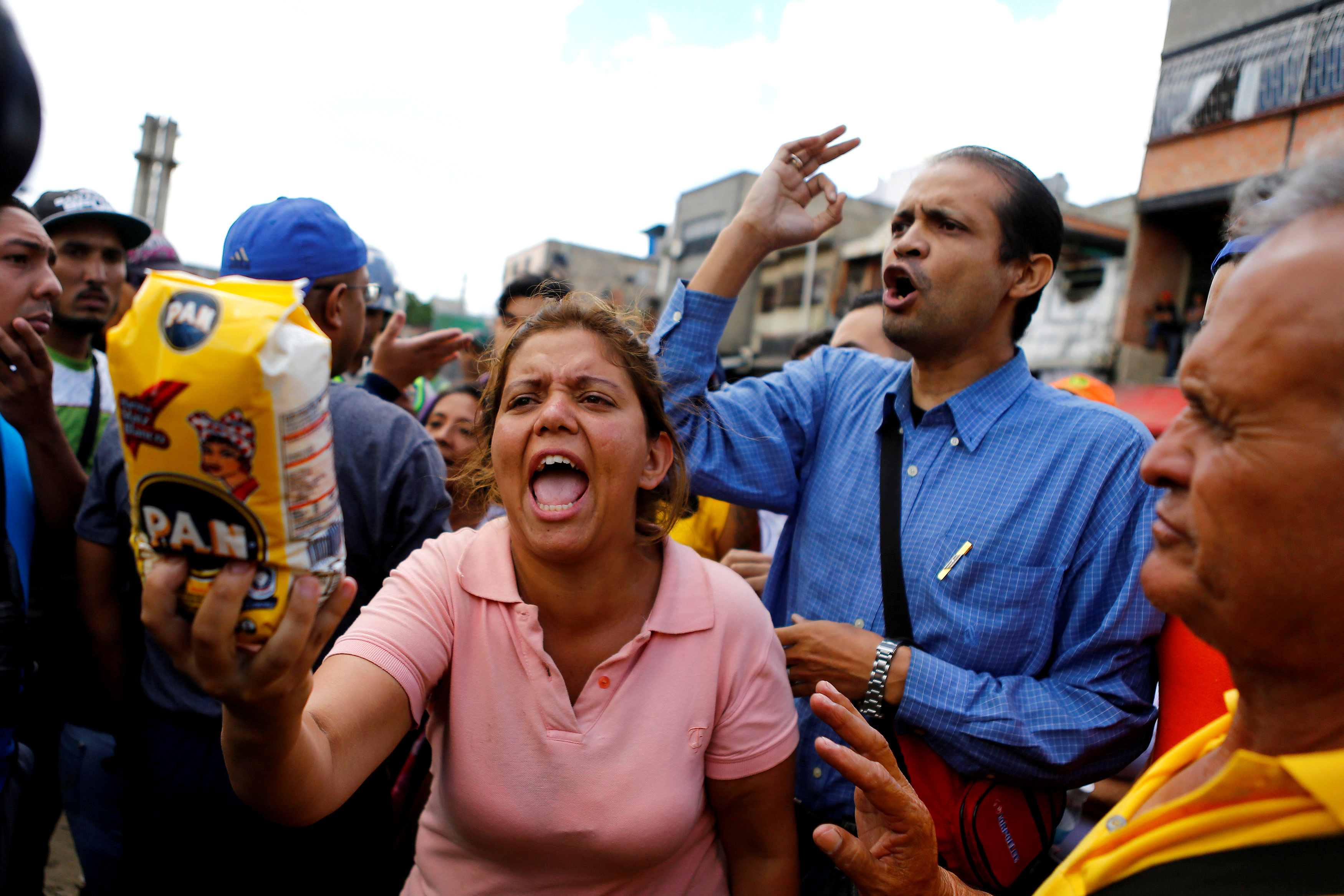 A woman shows a flour package outside a supermarket as they shout slogans over food shortage in Caracas, Venezuela