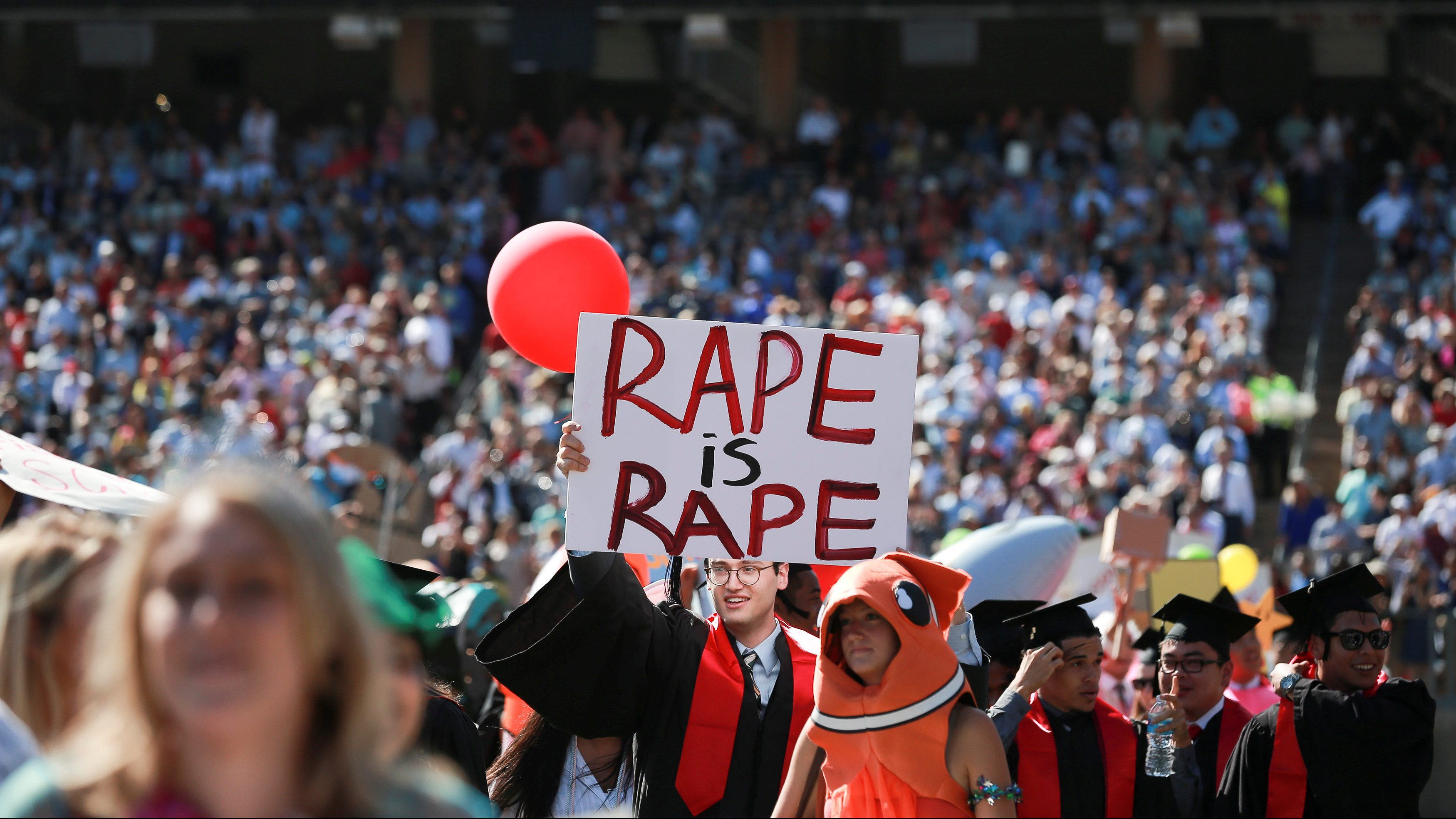 """A student holds a sign that reads: """"Rape is rape"""", during the Wacky Walk portion of the Stanford University commencement ceremony in Palo Alto, California, U.S. June 12, 2016."""