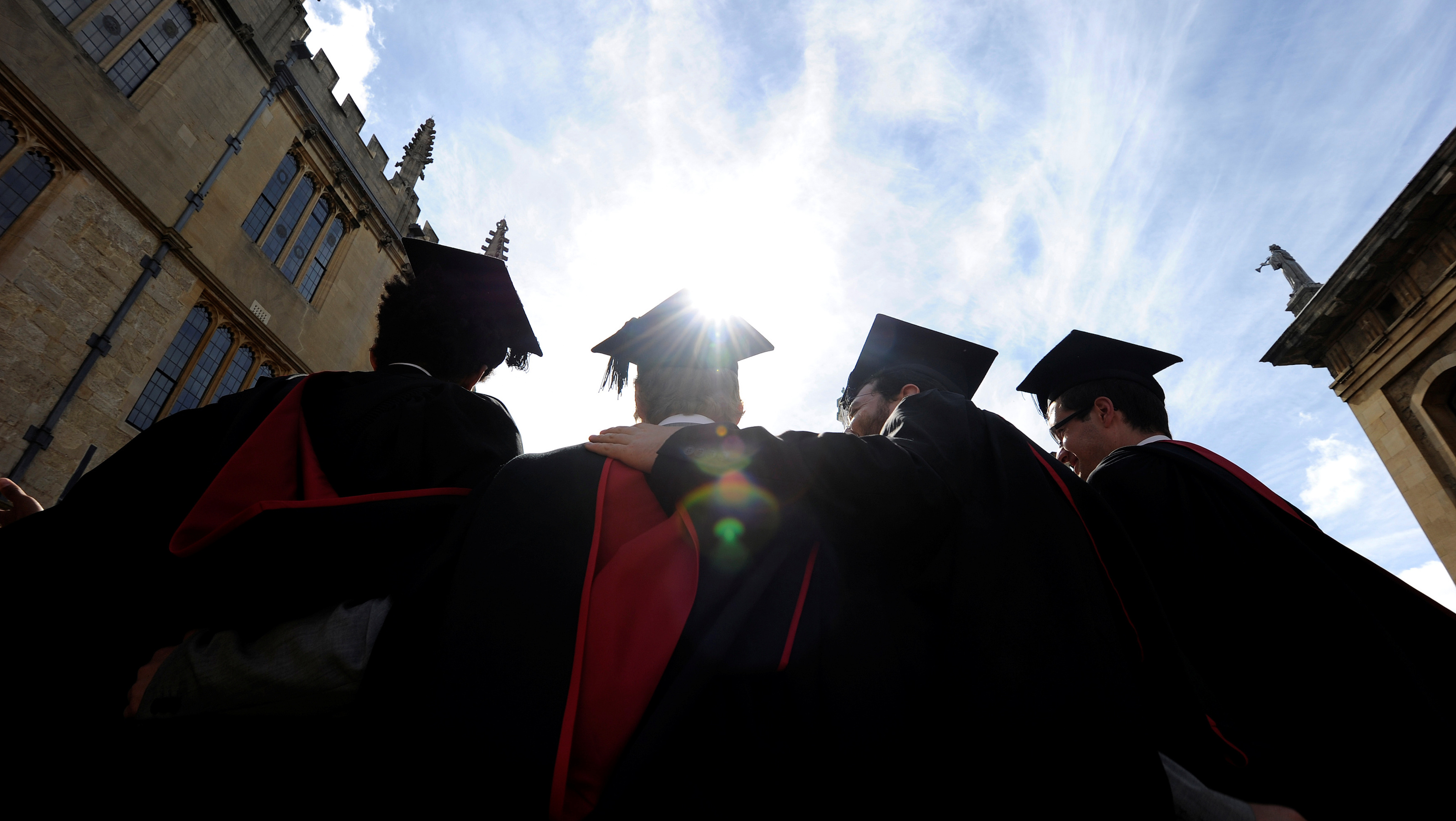 A group of graduates gather outside the Sheldonian Theatre to have their photograph taken after a graduation ceremony at Oxford University, Oxford, England, May 28, 2011. REUTERS/Paul Hackett/File Photo - RTX2IVBS