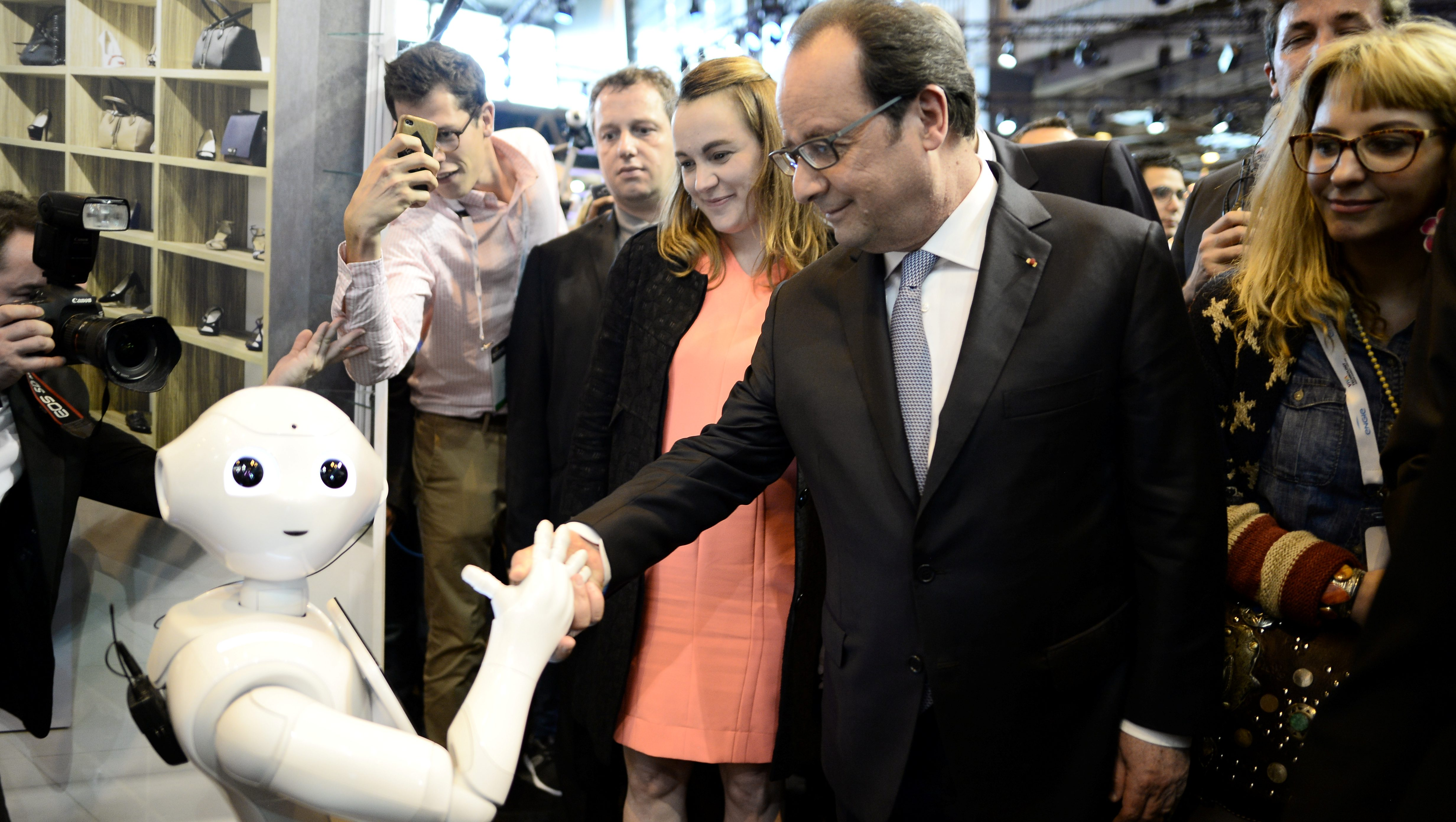 French President Francois Hollande (R) shakes hands with the IBM Watson powered robot during his visit to the Viva Technology event in Paris, France, June 30, 2016. REUTERS/Stephane de Sakutin/Pool  - RTX2J1E3