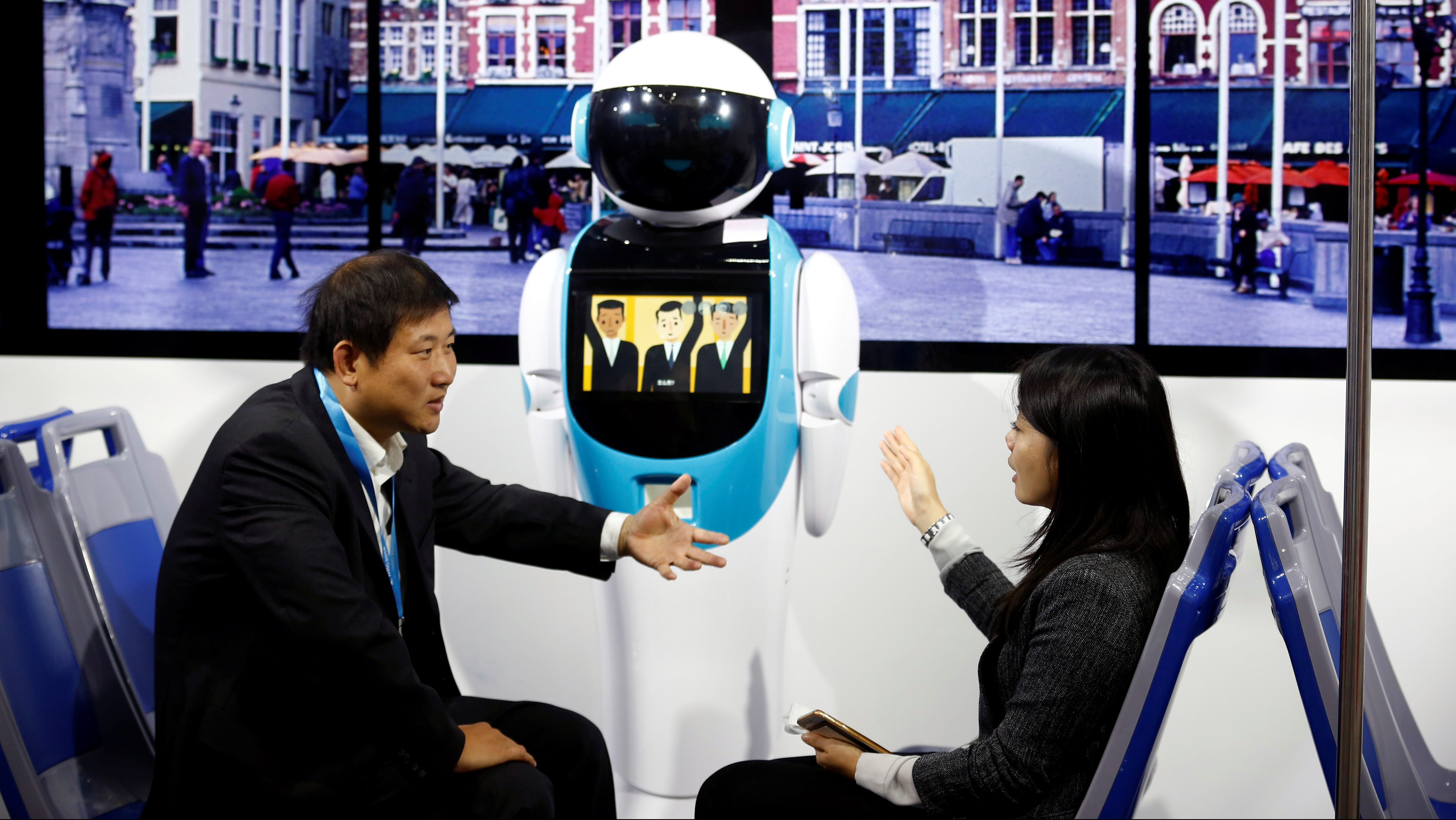 People talk as they sit in front of a robot in a public transport simulator at the WRC 2016 World Robot Conference in Beijing, China, October 21, 2016. REUTERS/Thomas Peter - RTX2PTN8