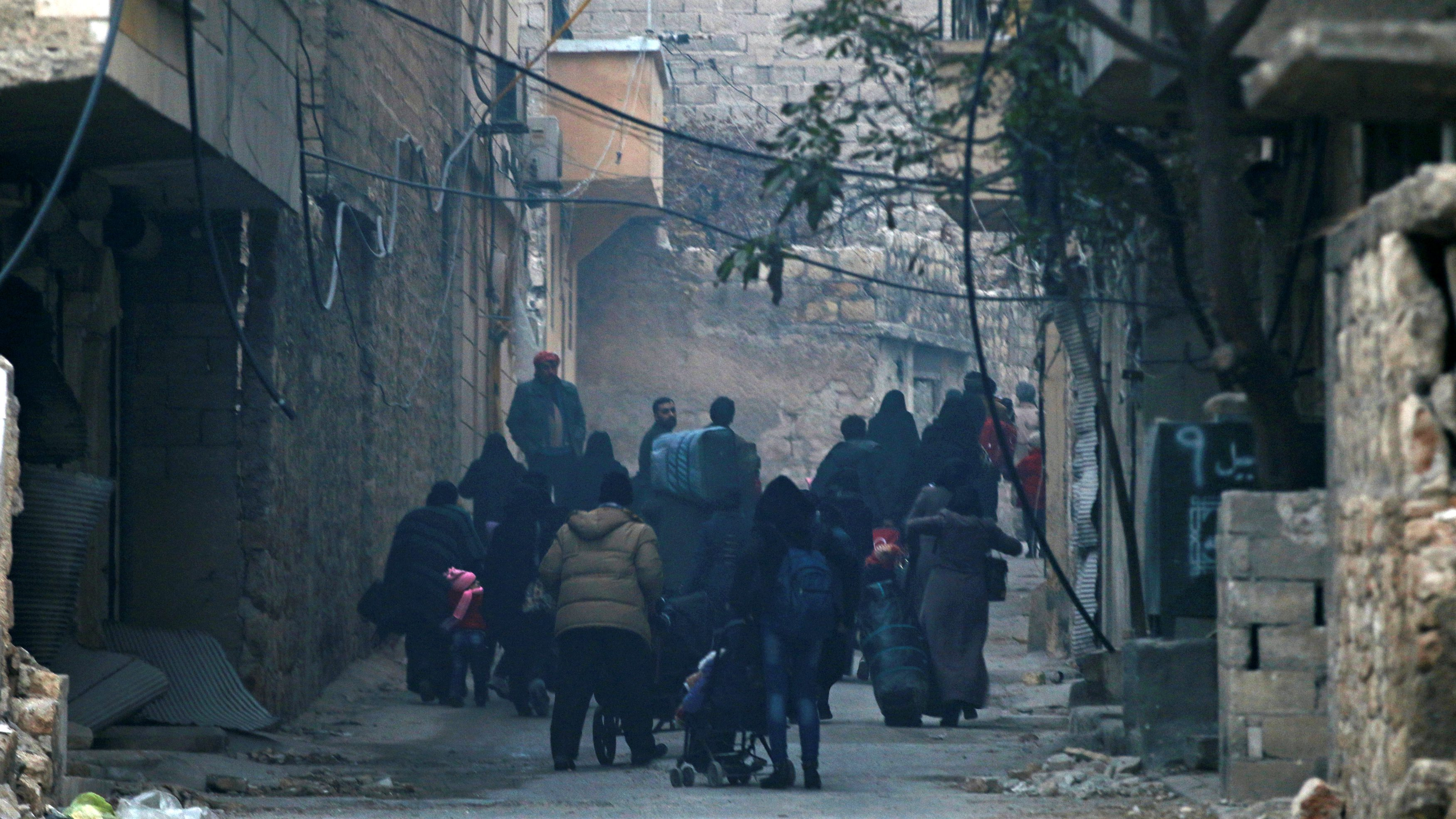 People carry belongings as they flee deeper into the remaining rebel-held areas of Aleppo