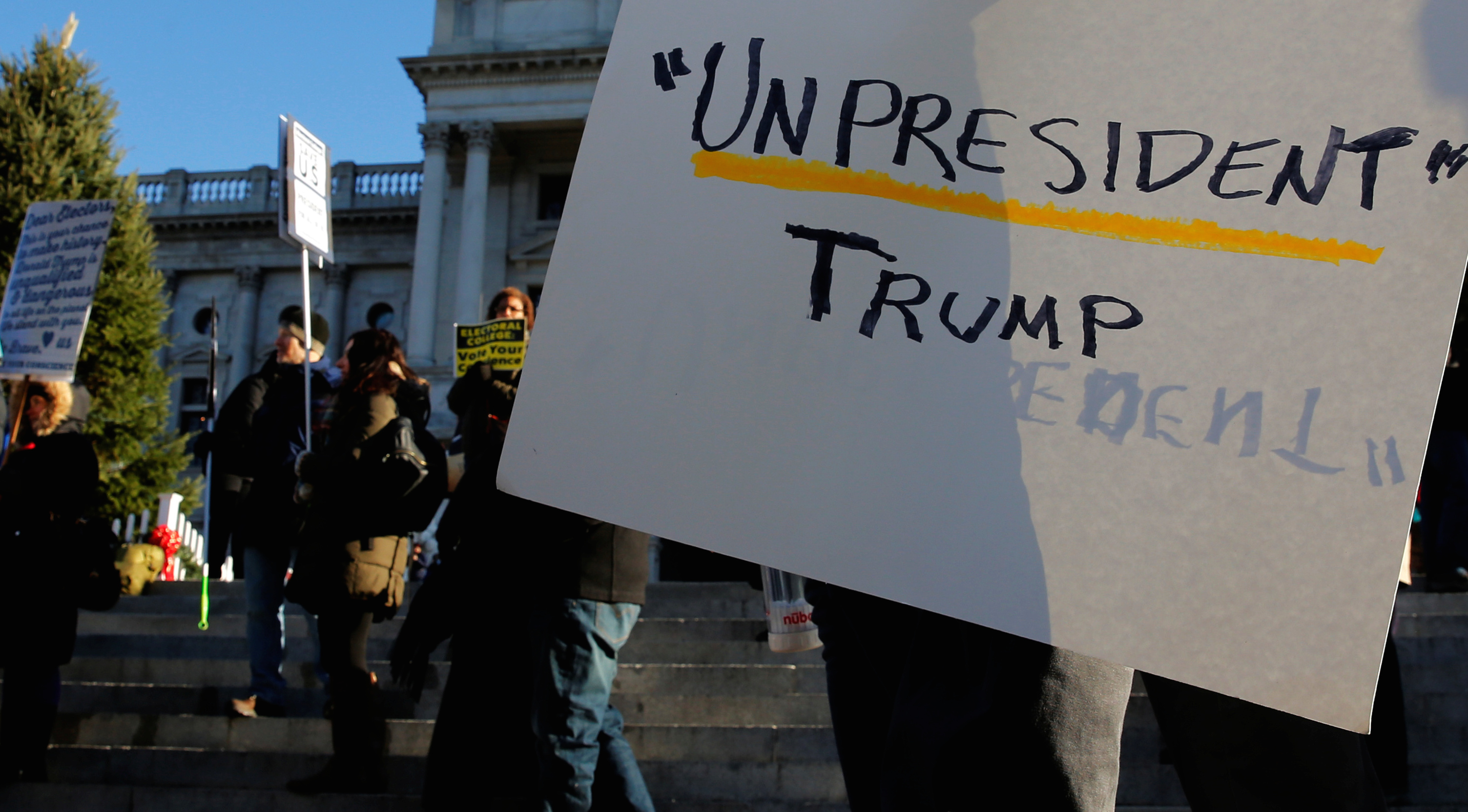 People protest against U.S. President-elect Donald Trump as electors gather to cast their votes for U.S. president at the Pennsylvania State Capitol in Harrisburg, Pennsylvania, U.S. December 19, 2016. Pennsylvania's twenty electors are assumed to be committed to Trump by virtue of his having won the popular vote in the state, but the vote that is usually routine takes place this year amid allegations of Russian hacking to try to influence the election.
