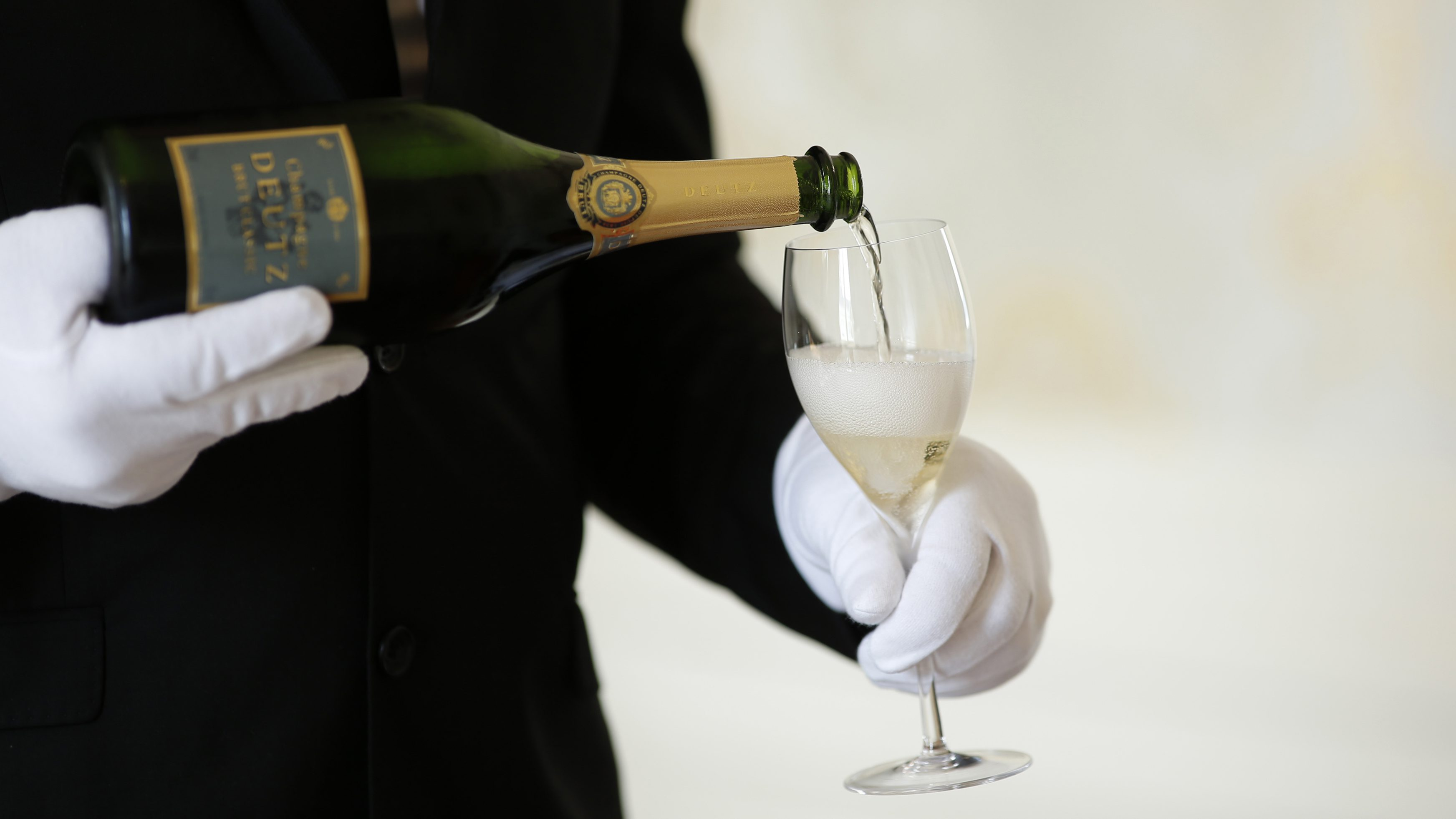 FILE PHOTO An employee serves a glass of Champagne during the traditional wine harvest at the Champagne house Deutz in Ay