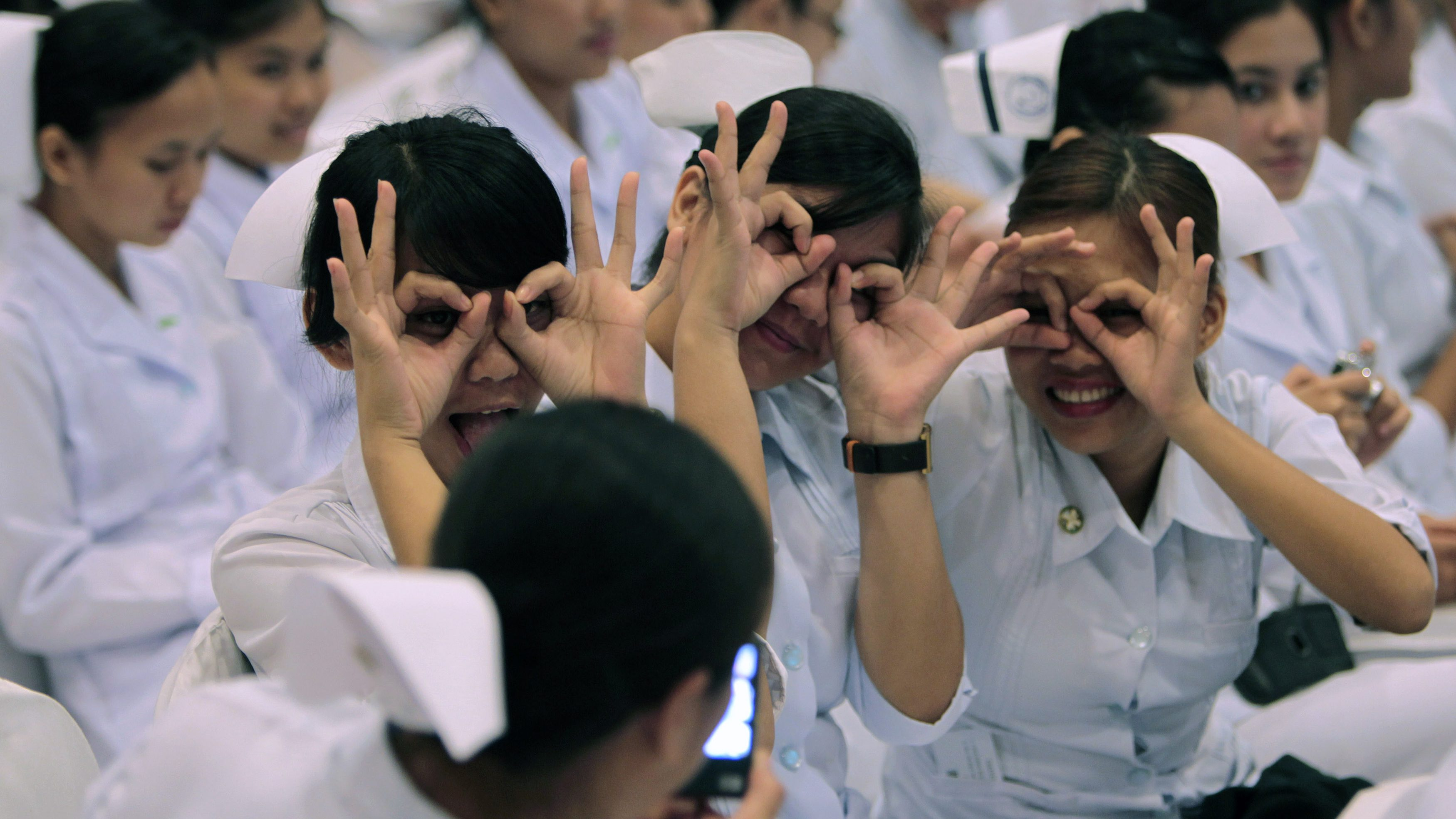 Newly graduated nurses gesture while having their picture taken by a friend before the oath taking ceremony of the professional nurses inside a mall in Manila