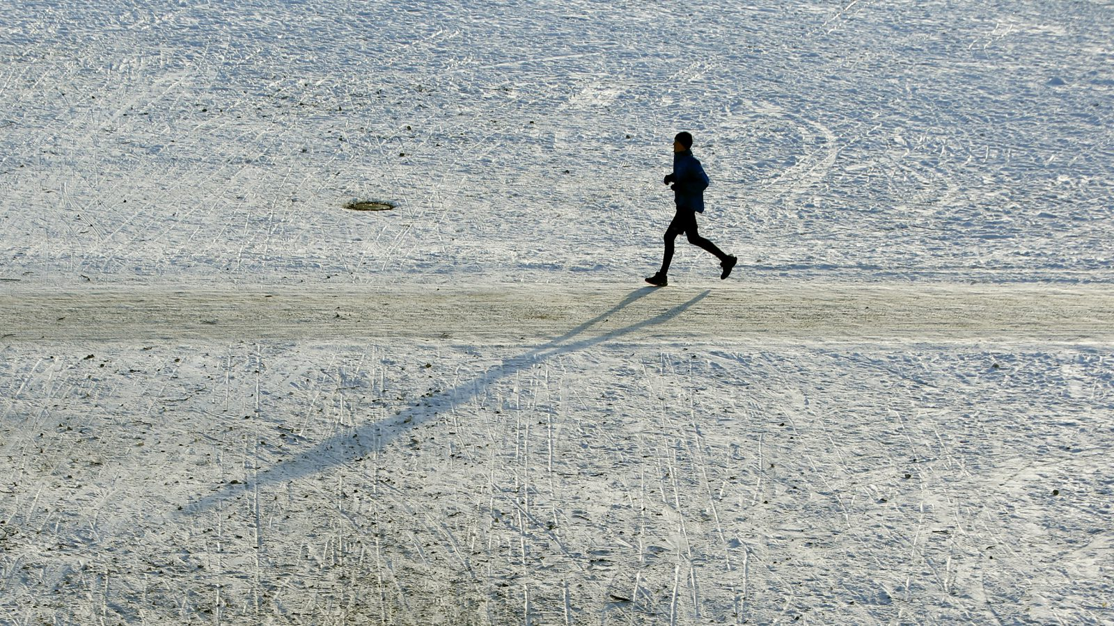 A jogger casts his shadow while running over the snow covered Theresienwiese in Munich, Germany, January 20, 2016.  REUTERS/Michaela Rehle - RTX236EX
