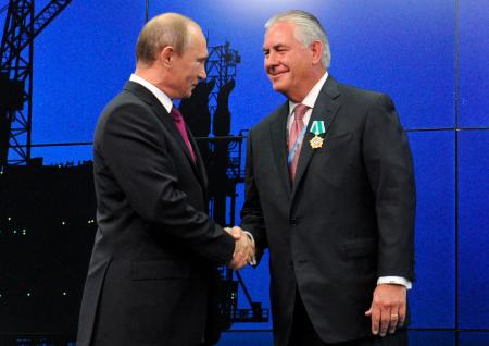 In this photo taken Thursday, June 21, 2012, Russian President Vladimir Putin presents ExxonMobil CEO Rex Tillerson with a Russian medal at an award ceremony of heads and employees of energy companies at the St. Petersburg economic forum in St. Petersburg, Russia. An aide to President Vladimir Putin praised United States President-elect Donald Trump's choice of Rex Tillerson to lead the State Department and says that the businessman is well regarded by many Russian officials.