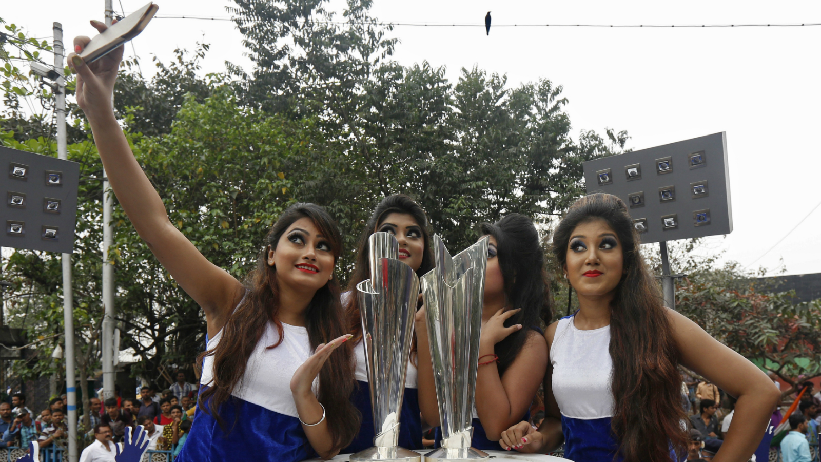 Models take a selfie next to the World Twenty20 trophies after they arrived in Kolkata, India, February 24, 2016. The two tournaments, Men's World Twenty20 and Women's World Twenty20 are scheduled to start on March 8 and March 15 respectively.