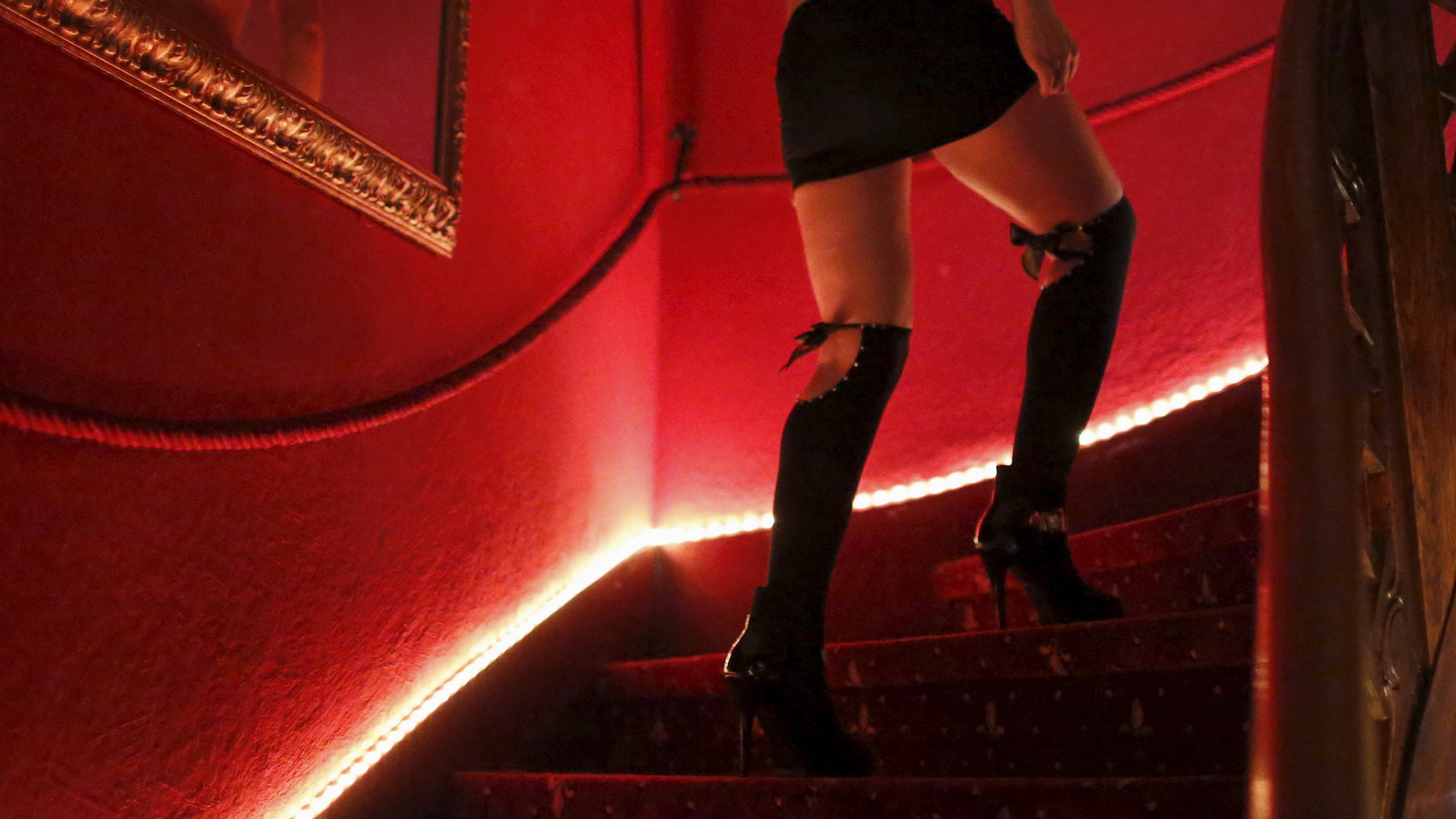 A woman in thigh-high heeled boots and a mini skirt walks up stairs lit with red lights.