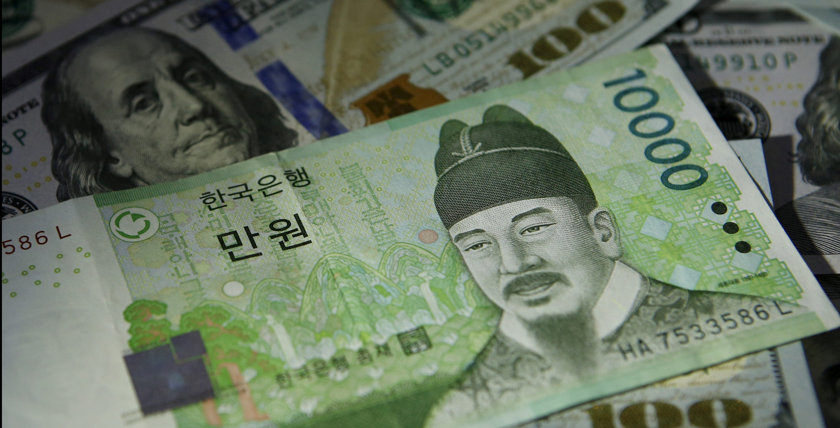 South Korean 10,000 won note is seen on U.S. 100 dollar notes in this picture illustration taken in Seoul, South Korea, December 15, 2015.