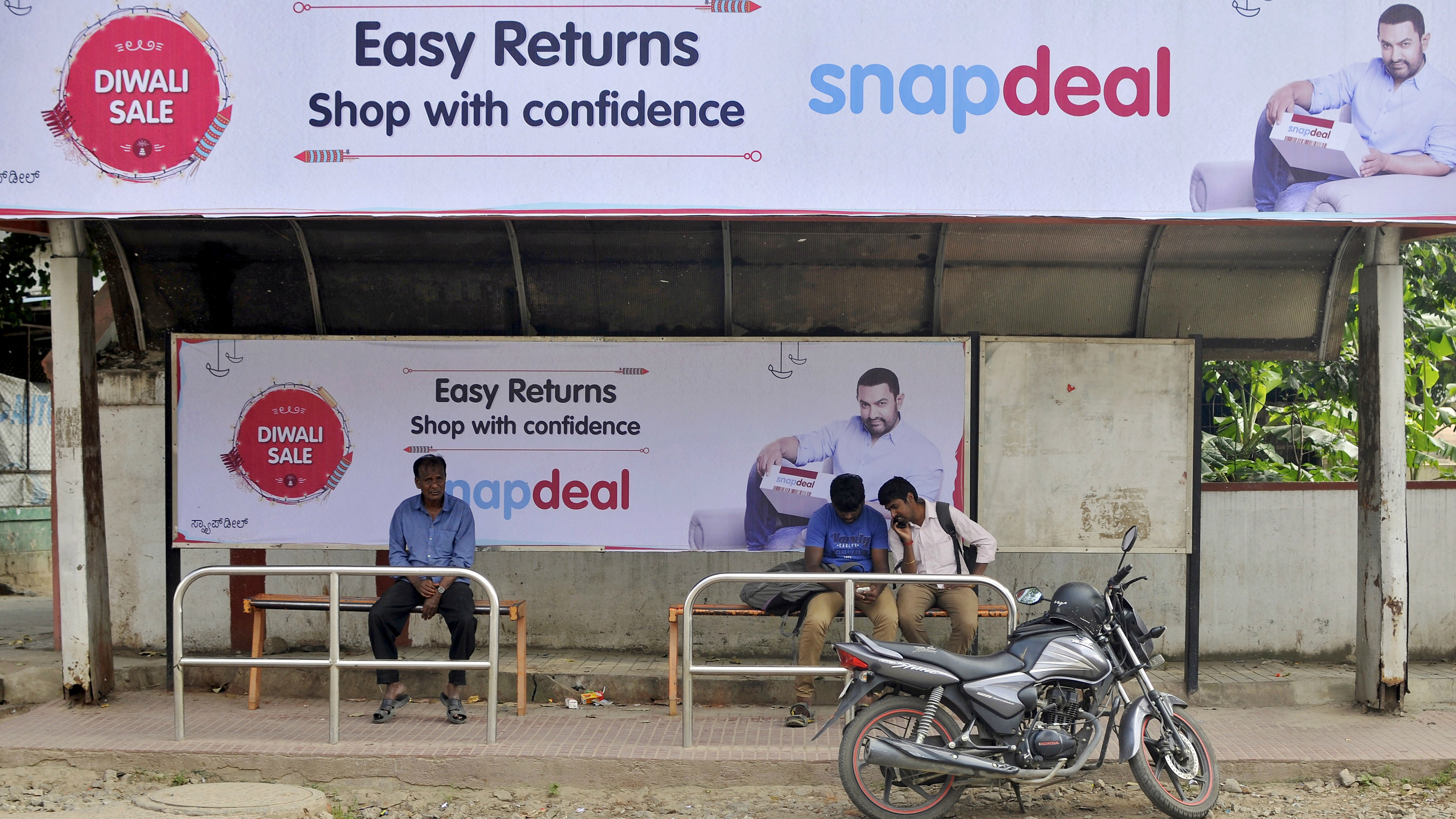 Commuters sit at a bus stop adorned with an advertisement of Indian online marketplace Snapdeal featuring Bollywood actor Aamir Khan, in Bengaluru, India, October 15, 2015. Amazon.com could emerge as the biggest winner from one of India's most important festive - and shopping - seasons that began this week, after the e-tailer offered steep discounts, swift delivery and even gold bars to grab market share. The month-long festive season culminates around November 10 in Diwali, or the Festival of Lights, but the first nine days are considered an especially auspicious time to make big purchases. Analysts say e-commerce firms in India could make as much as a quarter of their annual sales during this period, with the global experience, logistics network and deep pockets of Amazon putting it in a good position to grab customers from local market leader Flipkart and smaller firm Snapdeal. Picture taken October 15. REUTERS/Abhishek Chinnappa