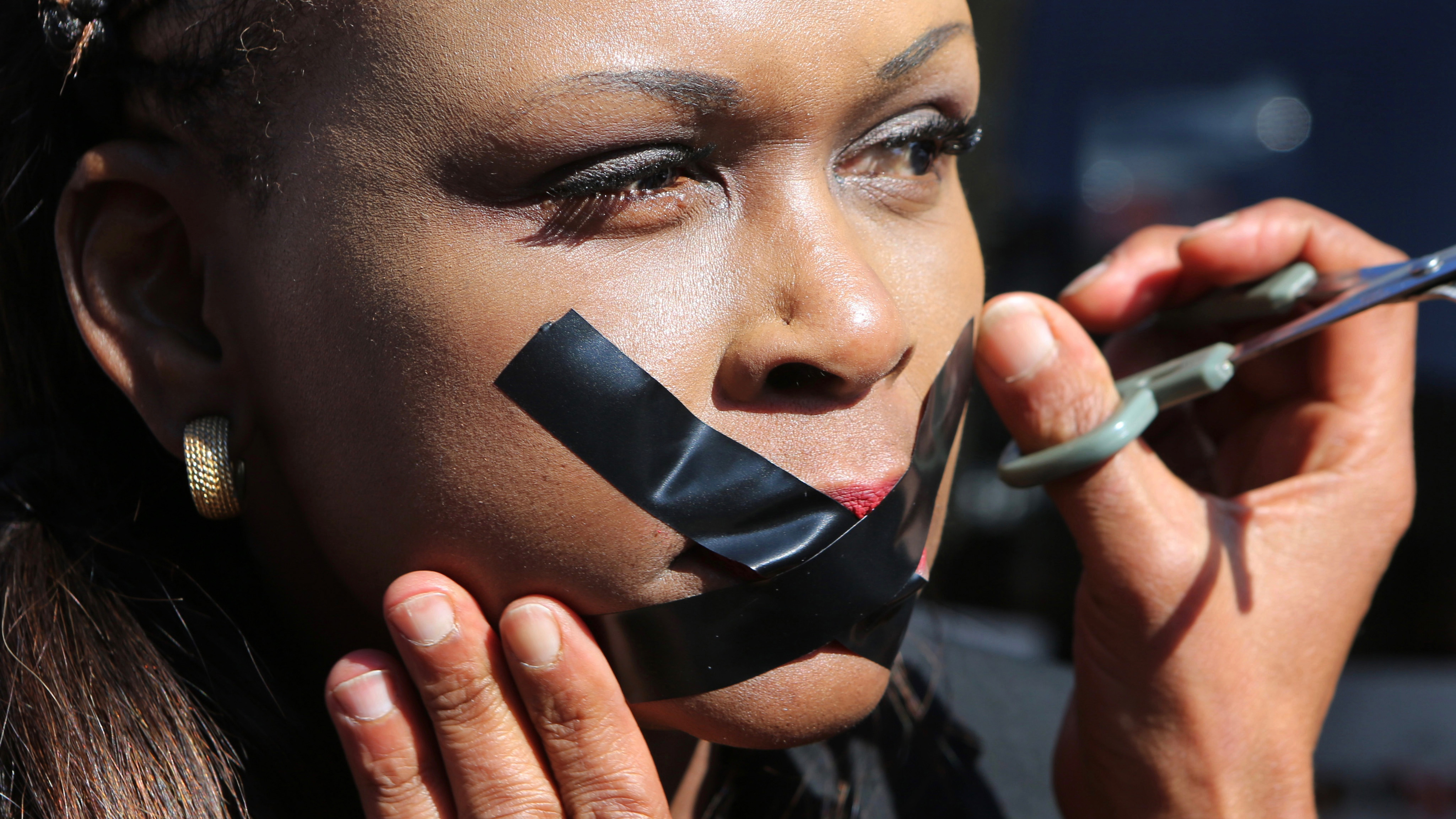 A protester has her lips taped in Johannesburg, Friday July 1, 2016, as journalists and members of the public demonstrate outside the South African Broadcasting Corporation (SABC) headquarters in solidarity with three SABC  journalists who were suspended for expressing their concerns about editorial policy amid allegations of newsroom censorship. (AP Photo/Denis Farrell).