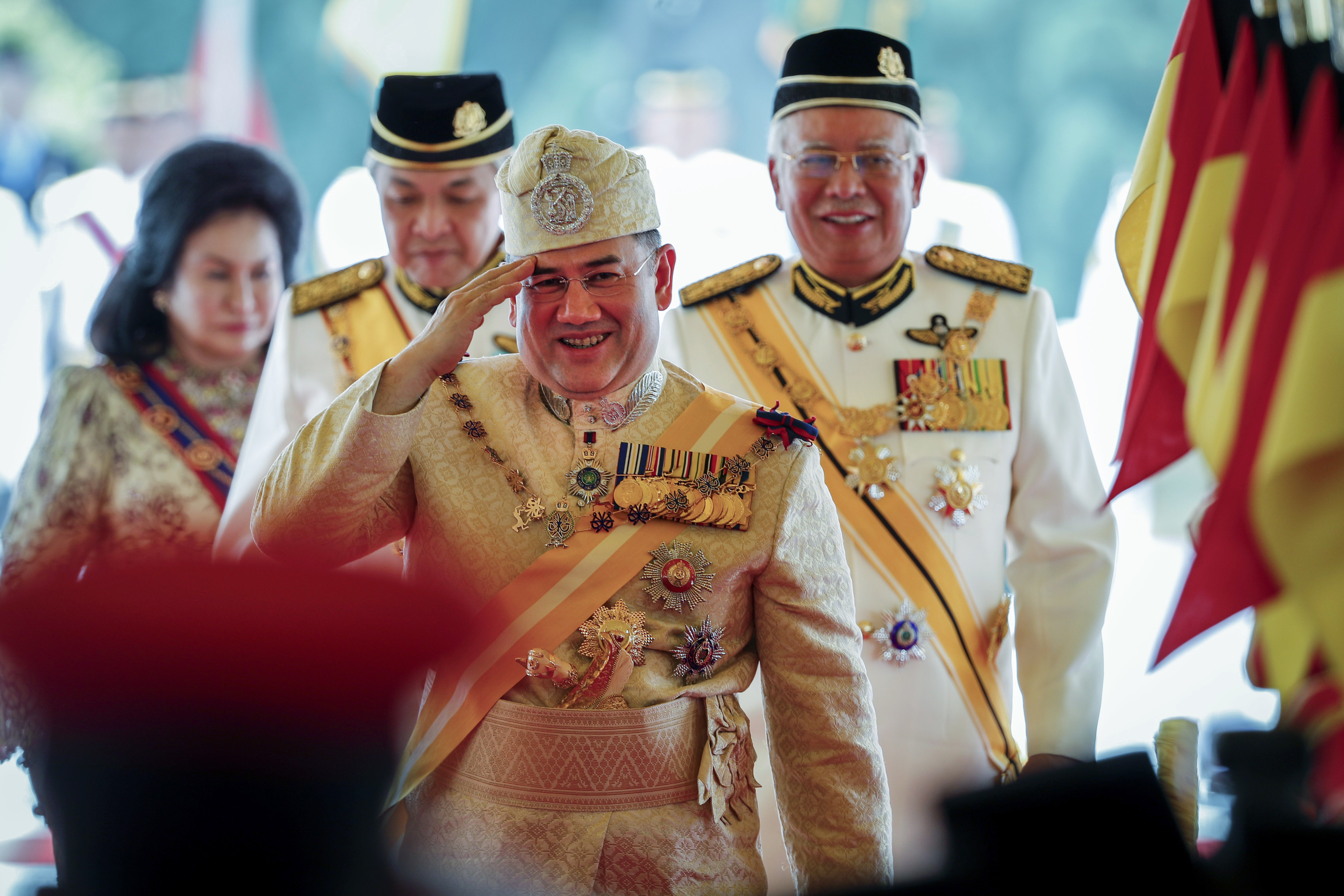 Sultan Muhammad V, center, salutes after his welcome ceremony as he walks with Malaysian Prime Minister Najib Razak, right, at the Parliament House in Kuala Lumpur, Malaysia, Tuesday, Dec. 13, 2016. Sultan Muhammad V of Kelantan will serve a five-year term as King of Malaysia from Tuesday. (AP Photo/Vincent Thian)