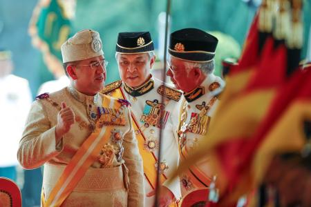 Sultan Muhammad V, left, chats with Malaysian Prime Minister Najib Razak, right, and Deputy Prime Minister Ahmad Zahid Hamidi, center, after his welcoming ceremony at the Parliament House in Kuala Lumpur, Malaysia, Tuesday, Dec. 13, 2016. Sultan Muhammad V of Kelantan will serve a five-year term as King of Malaysia from Tuesday. (AP Photo/Vincent Thian)