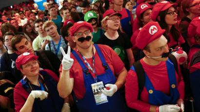 "Cosplayers dressed as character ""Mario"" celebrate the 30th anniversary of ""Super Mario Bros."" video games developed by Nintendo during the Gamescom 2015 fair in Cologne"