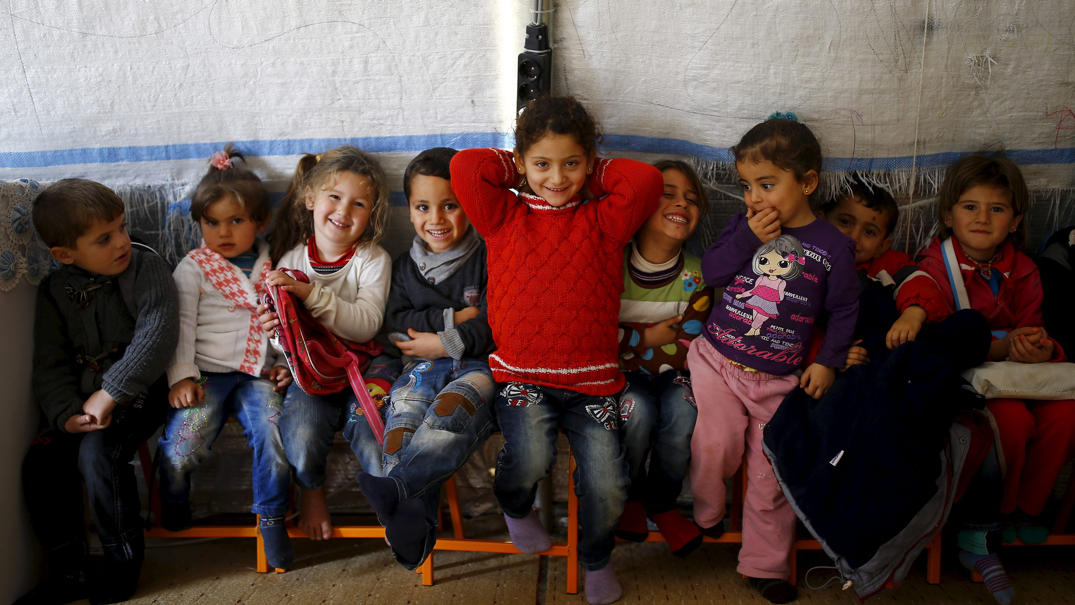Syrian refugee girl Ele Cundi, 5, poses as she sits with her friends in a kindergarten at Midyat refugee camp in Mardin province, Turkey, December 14, 2015. Syria's conflict has left hundreds of thousands dead, pushed millions more into exile, and had a profound effect on children who lost their homes or got caught up in the bloodletting. The drawings of young refugees living in Turkey show their memories of home and hopes for its future. The pictures also point to the mental scars borne by 2.3 million Syrian refugees living in Turkey, more than half of them children.